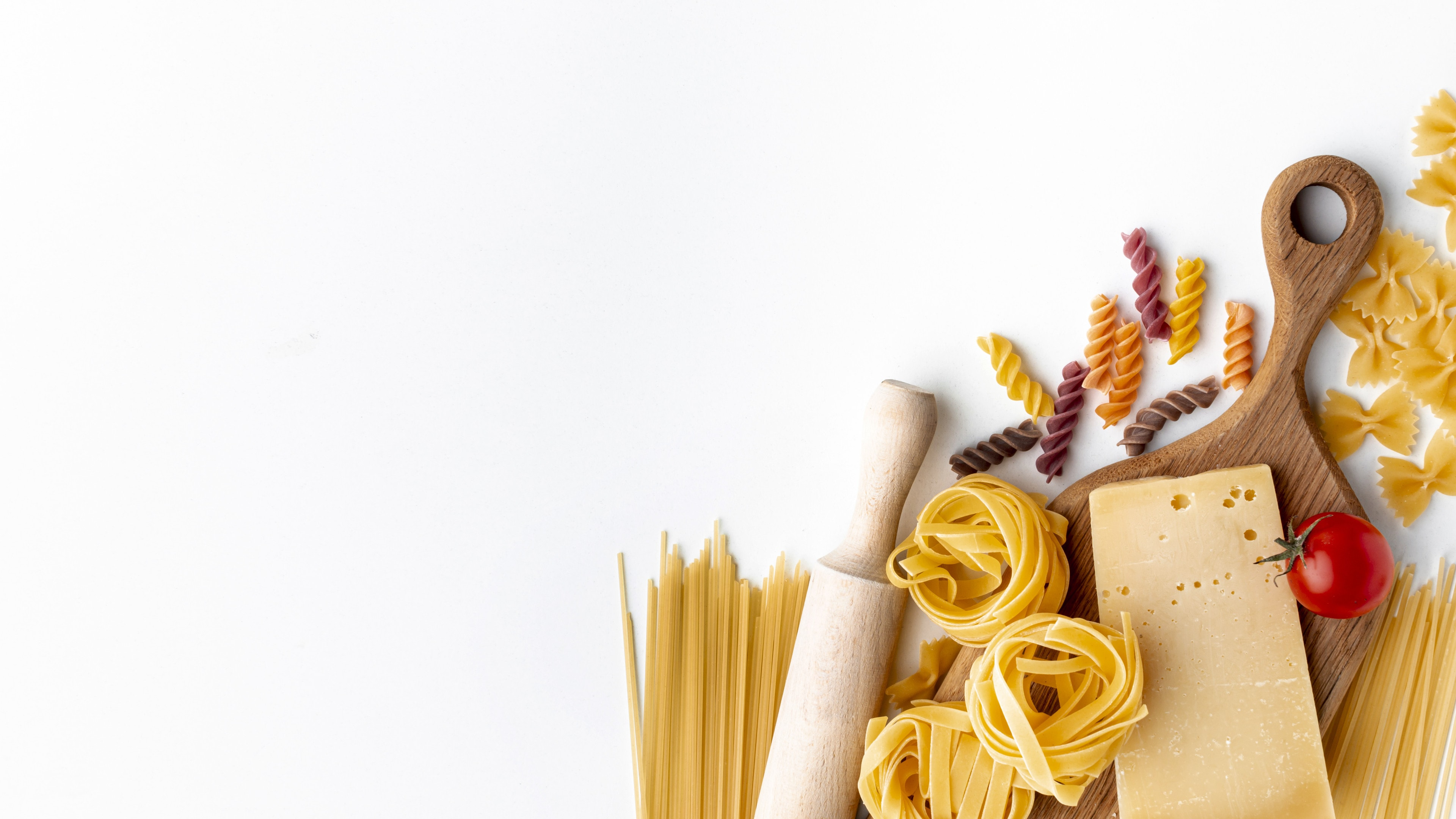 Mix of uncooked pasta and hard cheese on white background