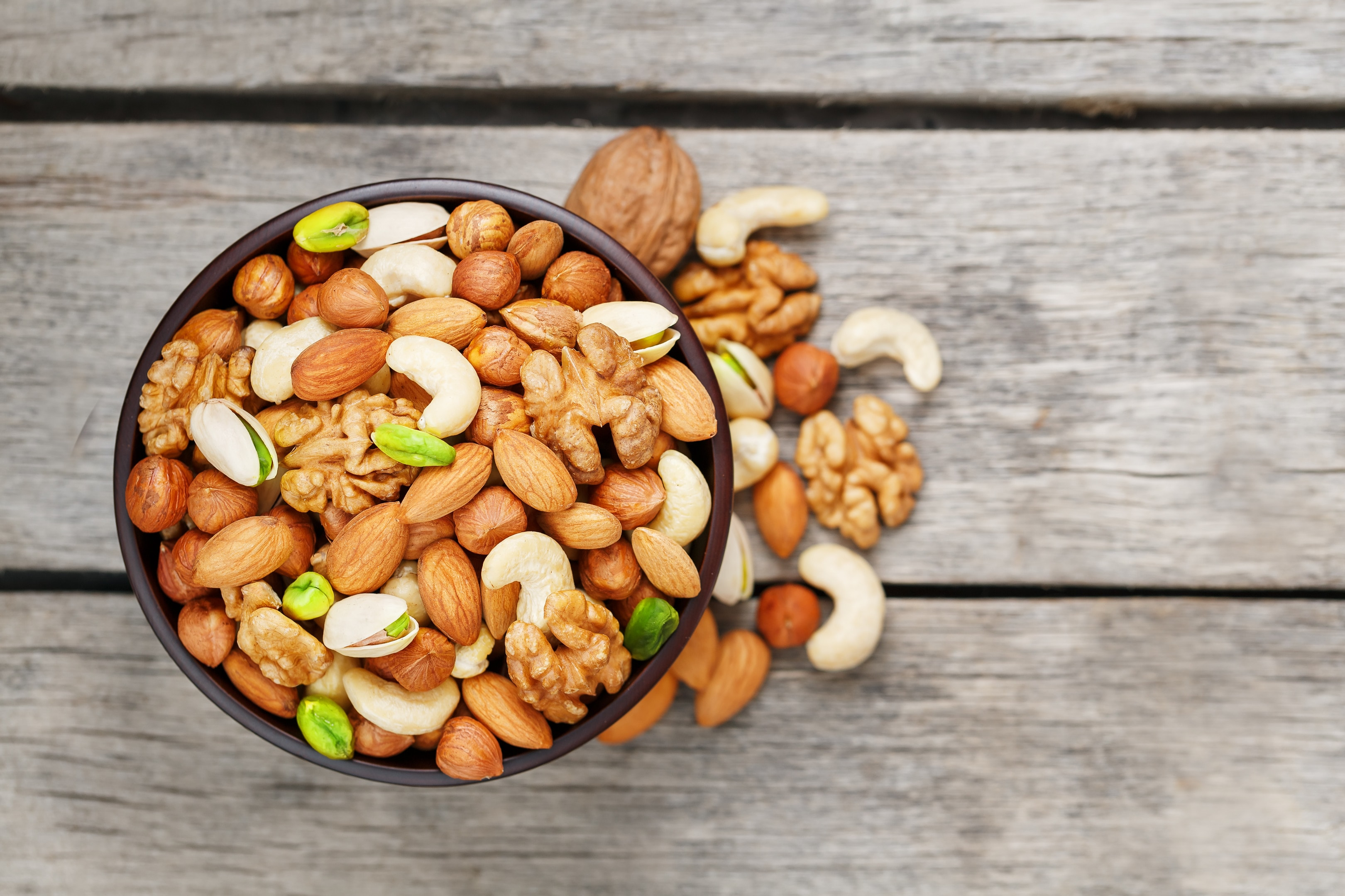Mixed nuts walnut pistachios almonds hazelnuts cashews in wooden bowl