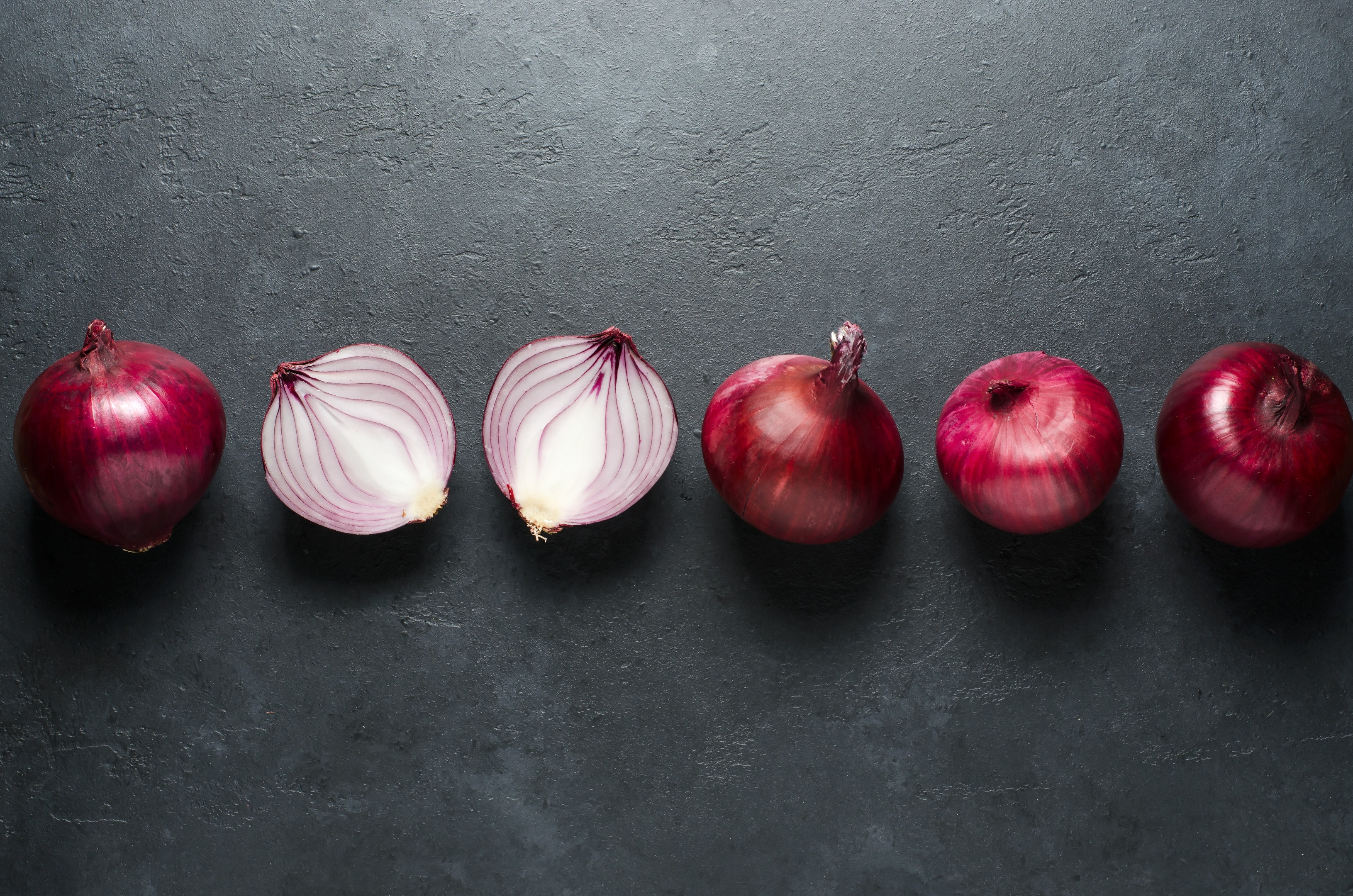 Red onion whole and sliced on black background