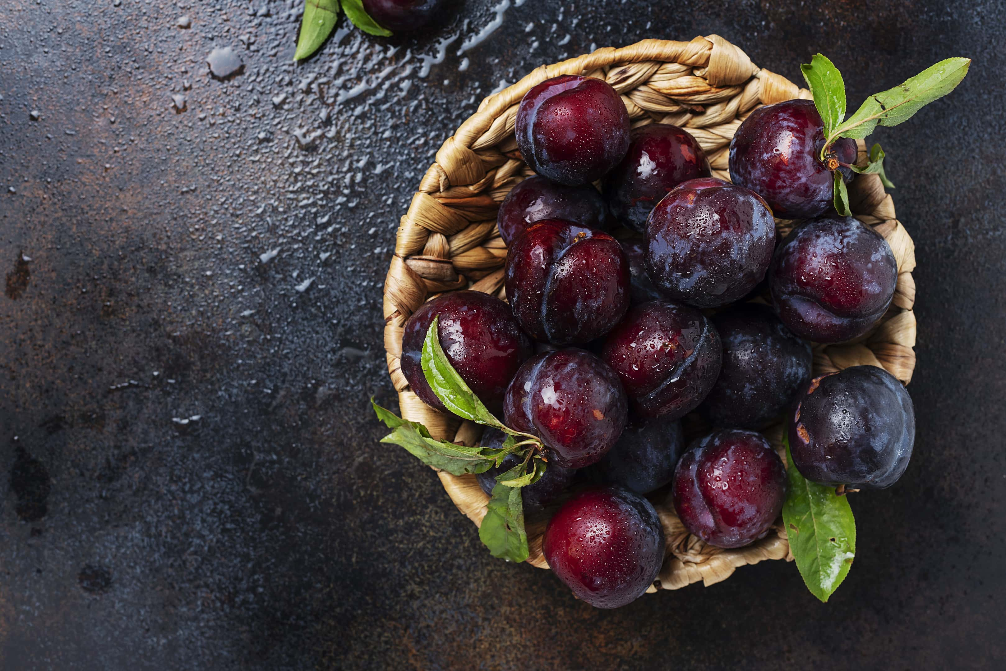 Ripe plums in wooden bowl