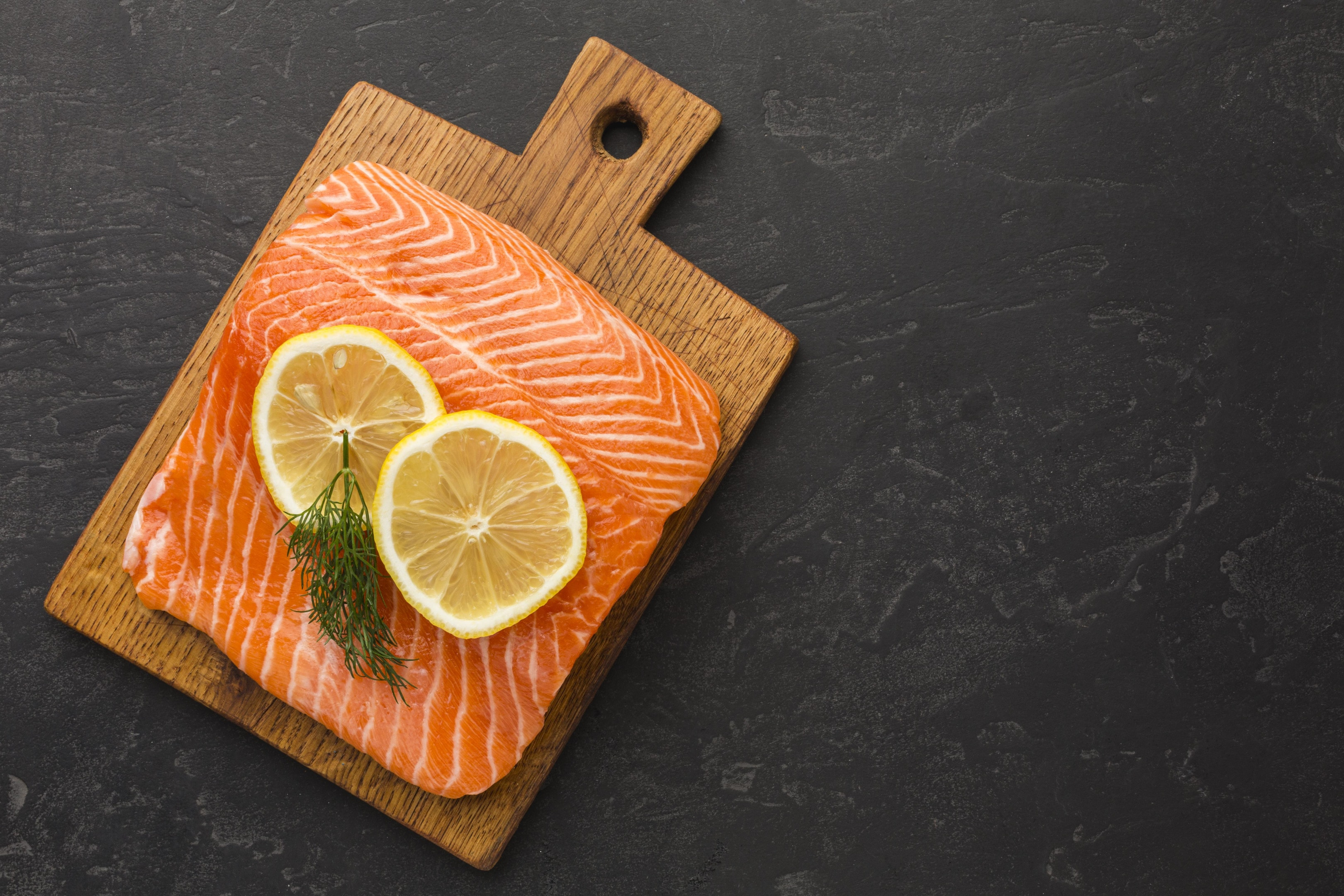 Salmon and lemon on wooden board