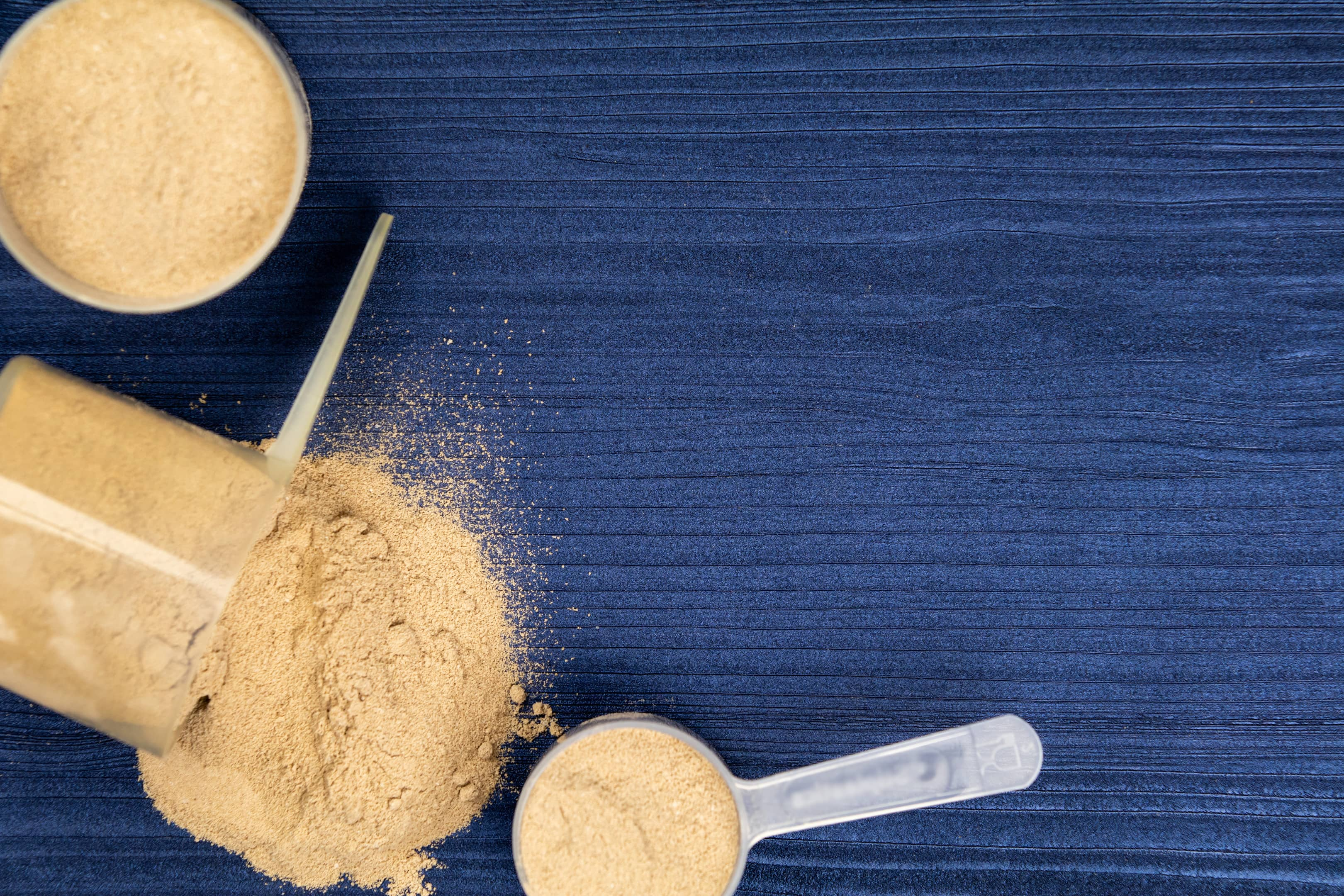 Scoops filled whey protein powders on blue background