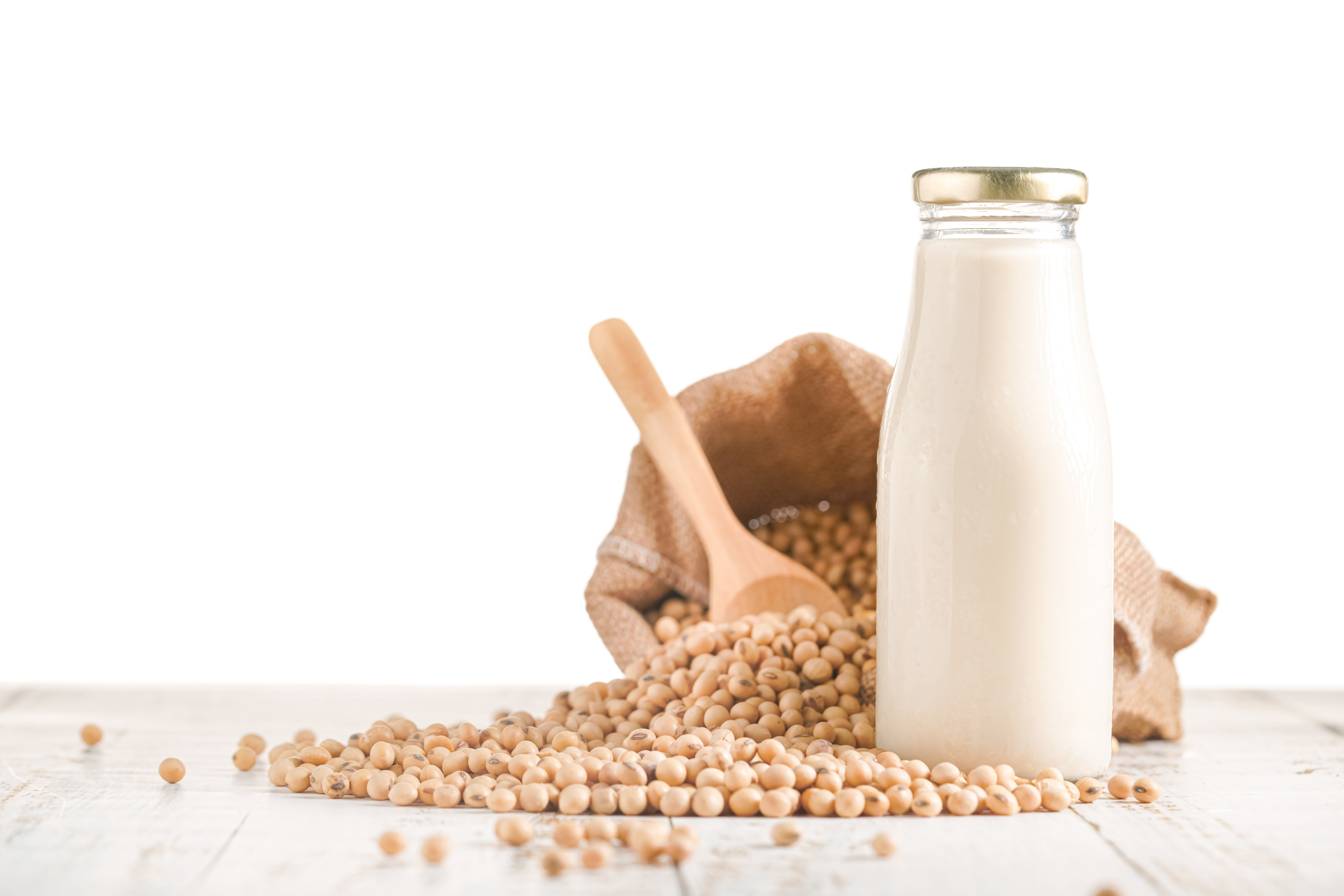 Soy beans and bottle of soy milk on white background