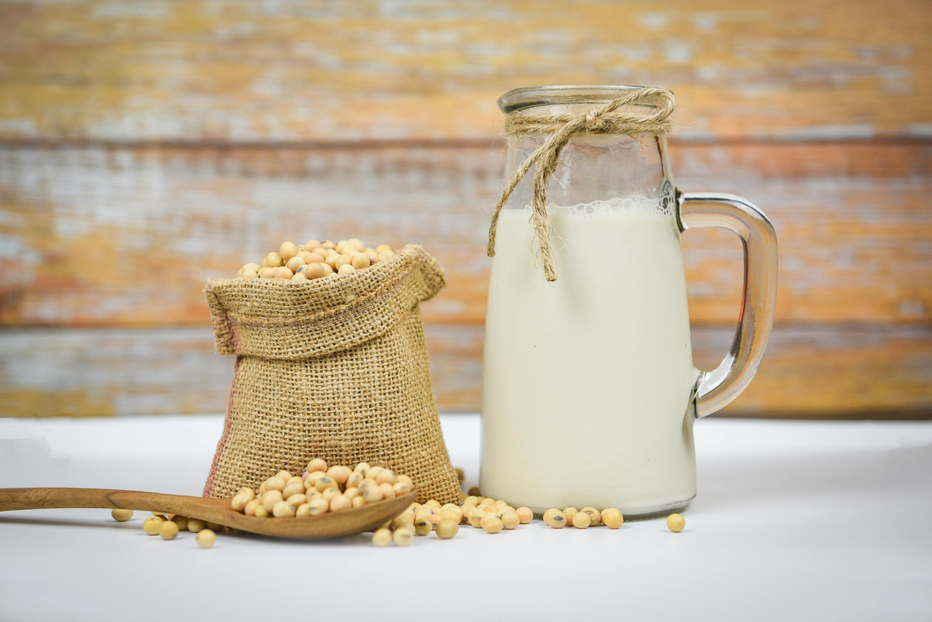 Soy beans and soy milk on white table