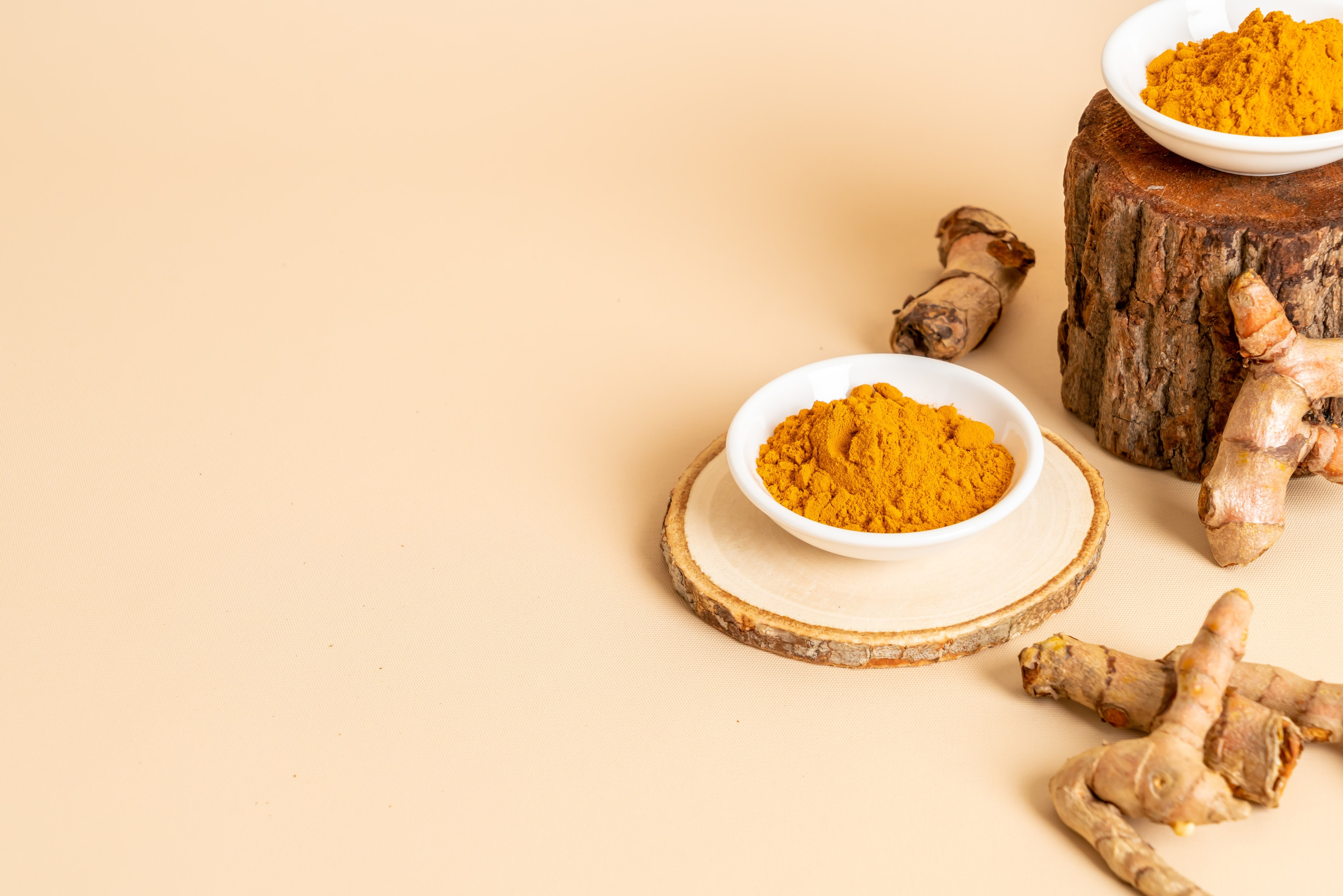 Turmeric powder and fresh turmeric on pastel background