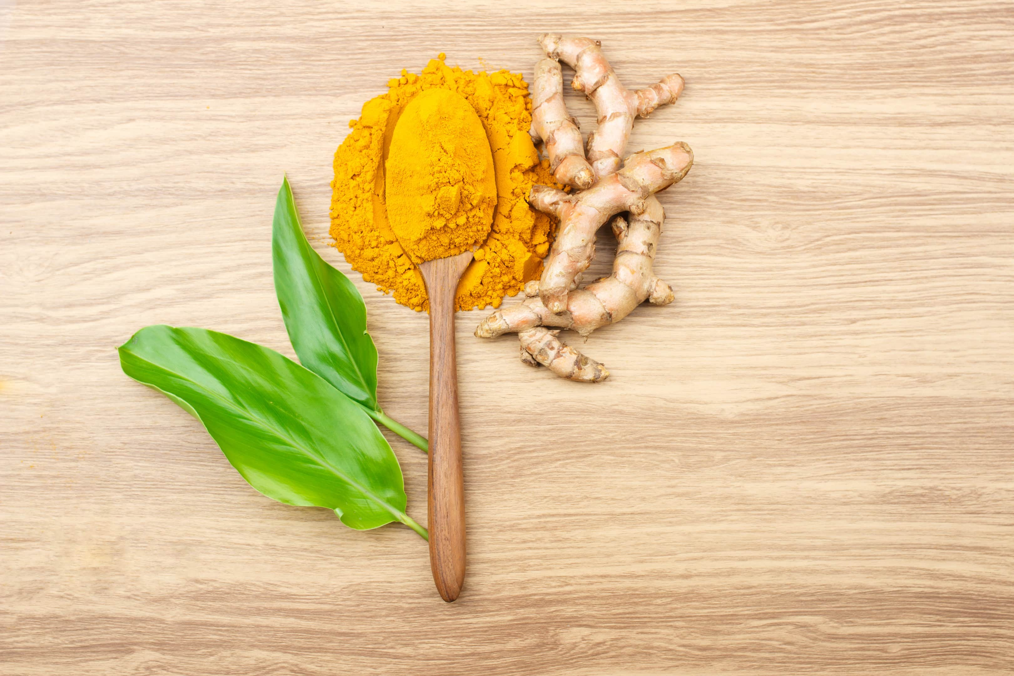 Turmeric root and powder on wooden table