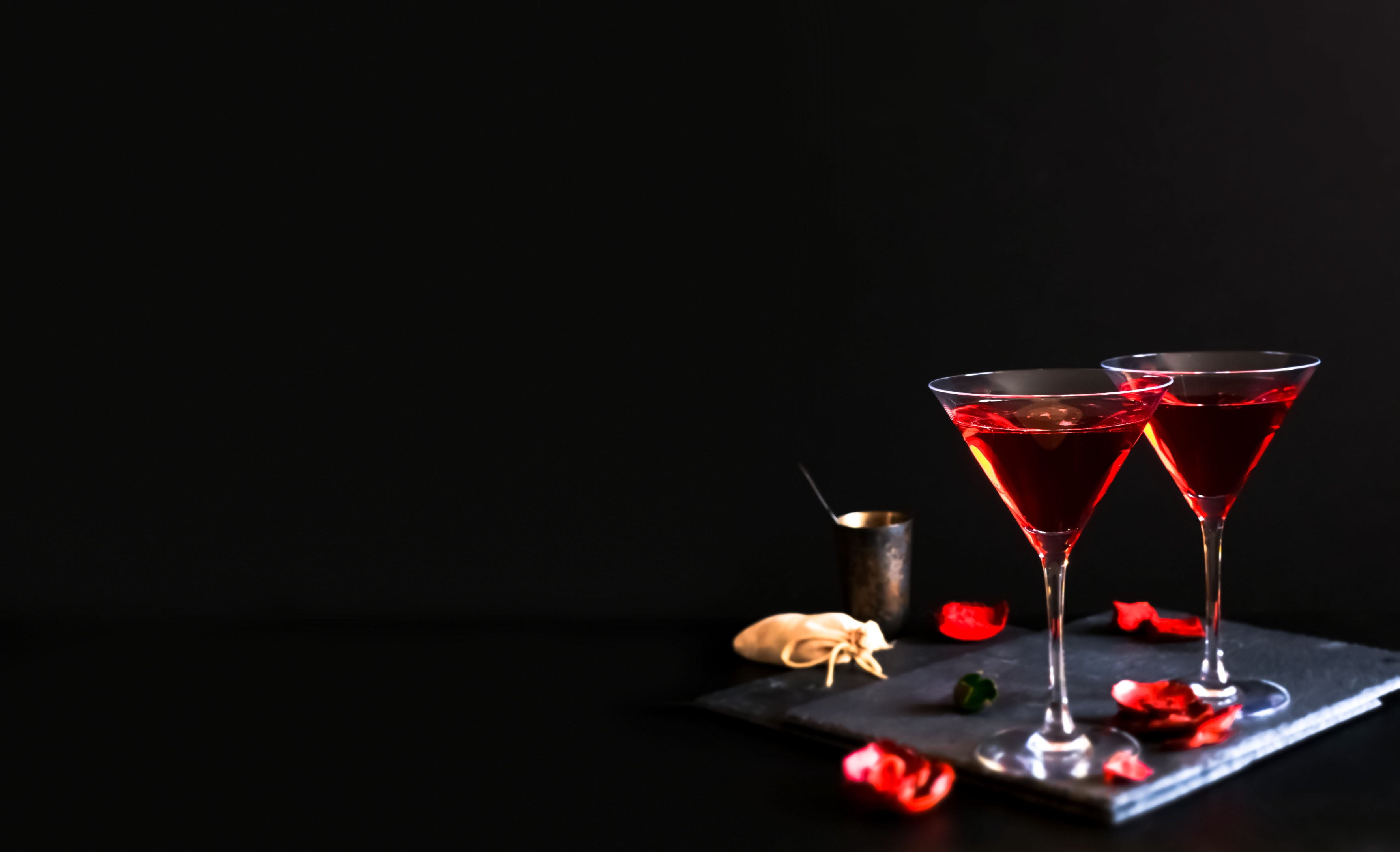 Two cosmopolitan cocktails in triangular glass
