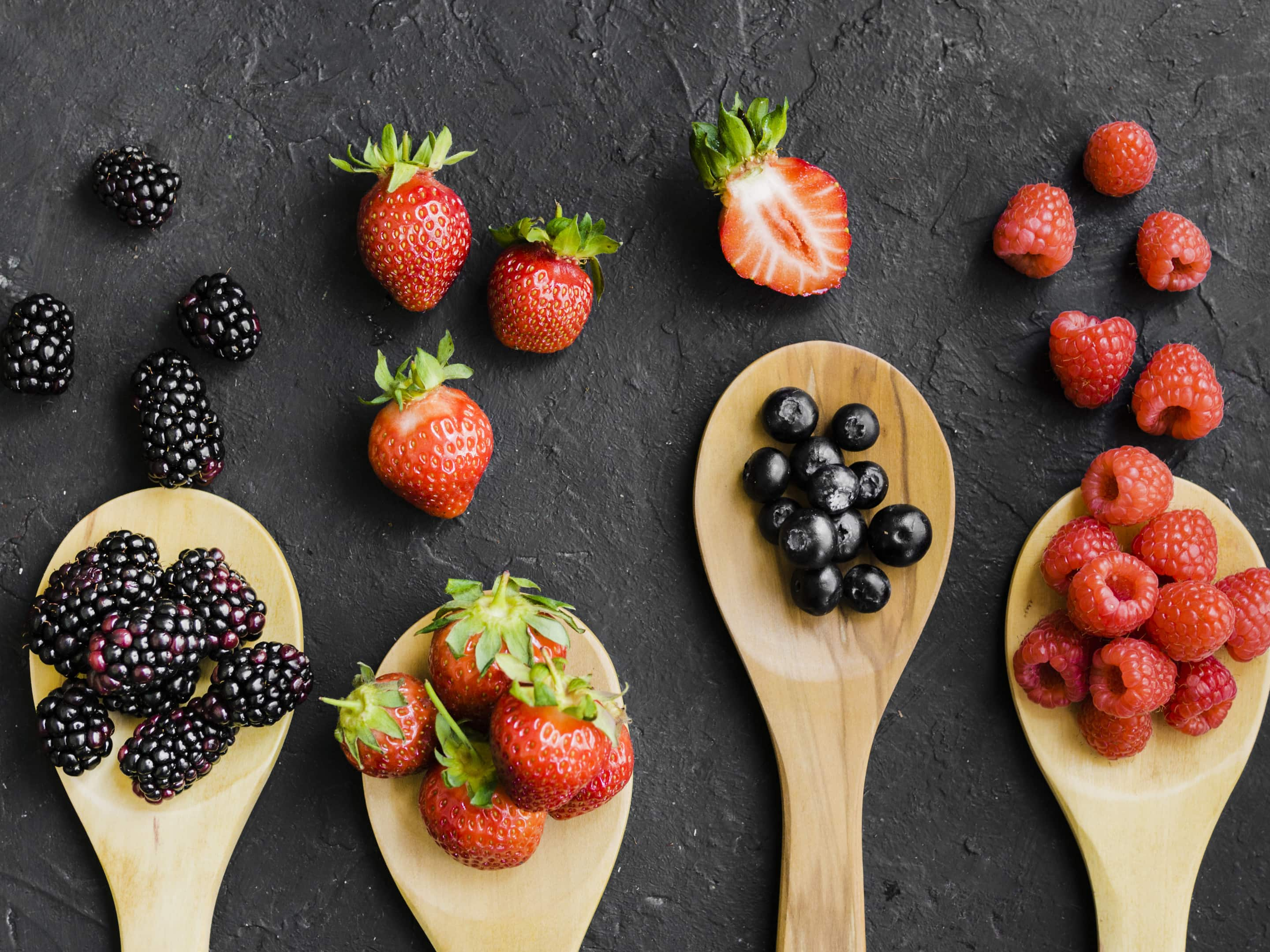 Variety of berries on wooden spoons