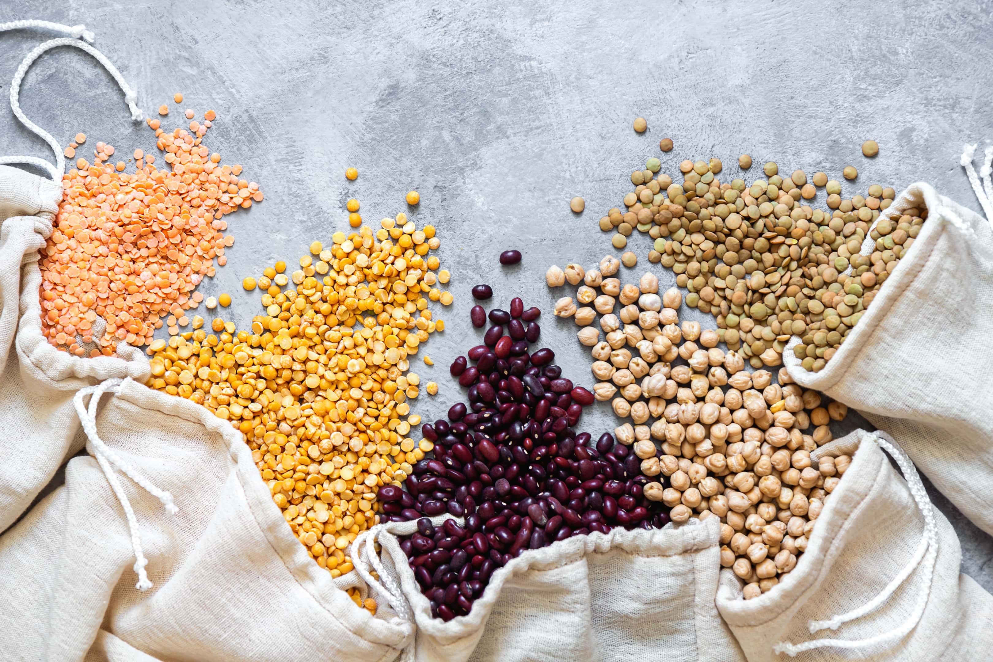 Various legumes spill from eco bags