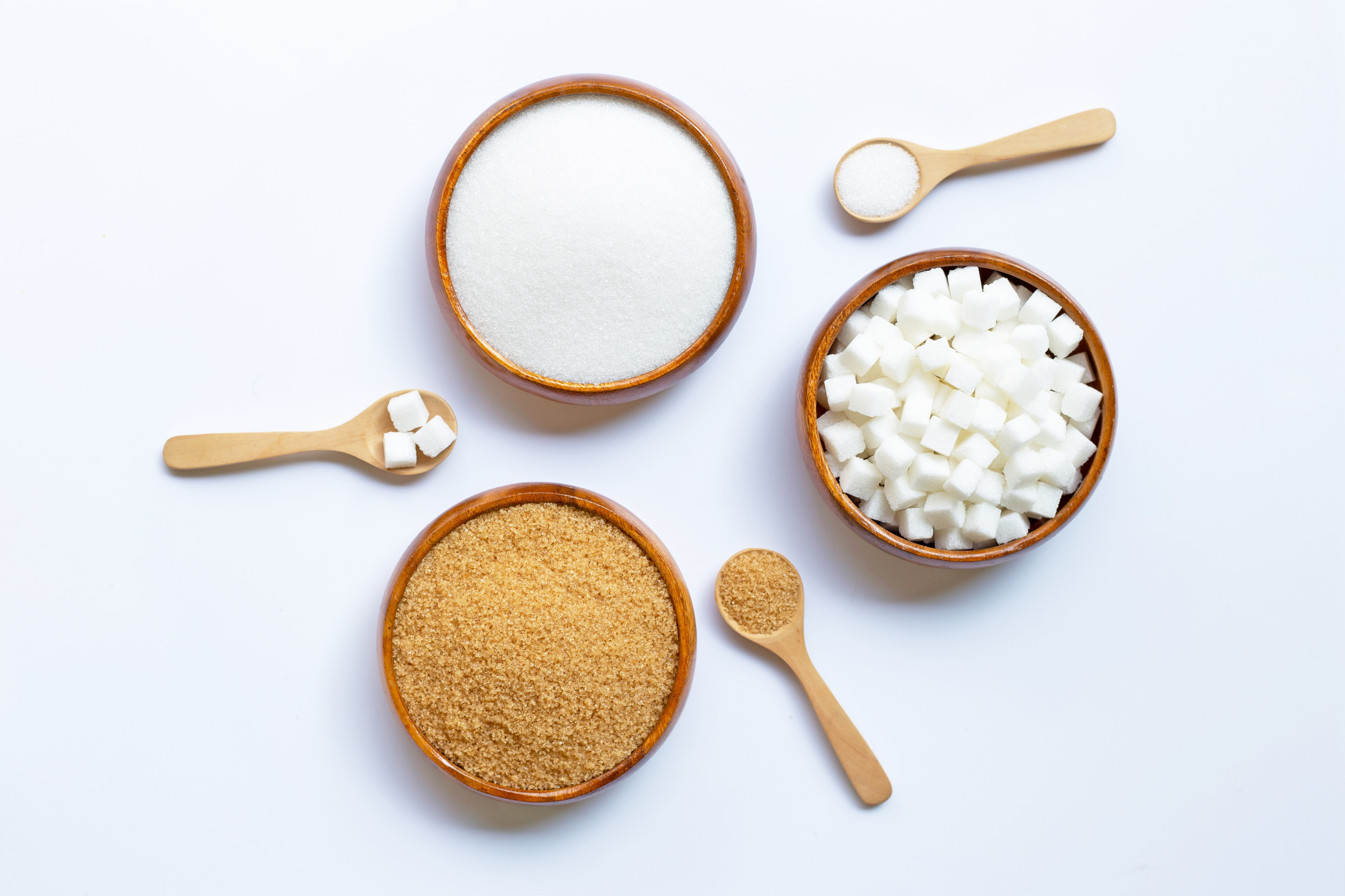 Various types sugar in wooden bowls on white background