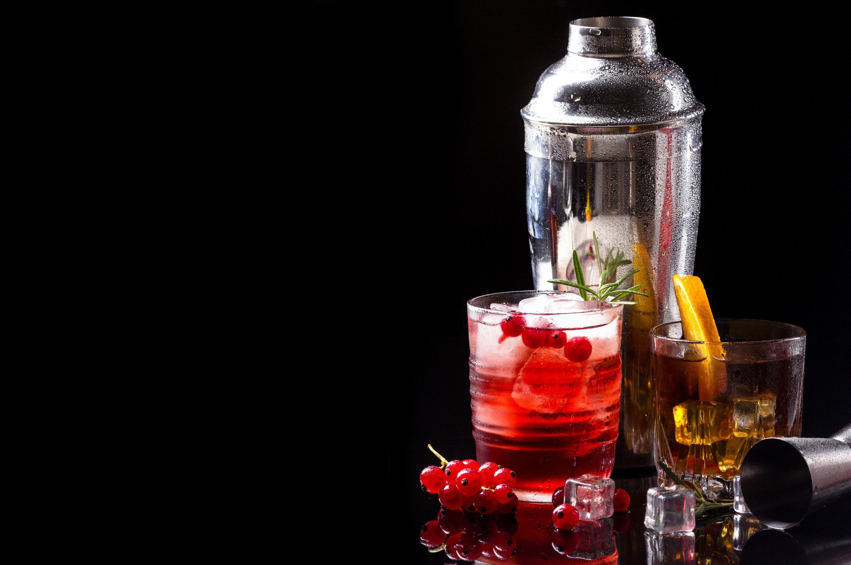 Vodka cranberry and whiskey with orange on black background