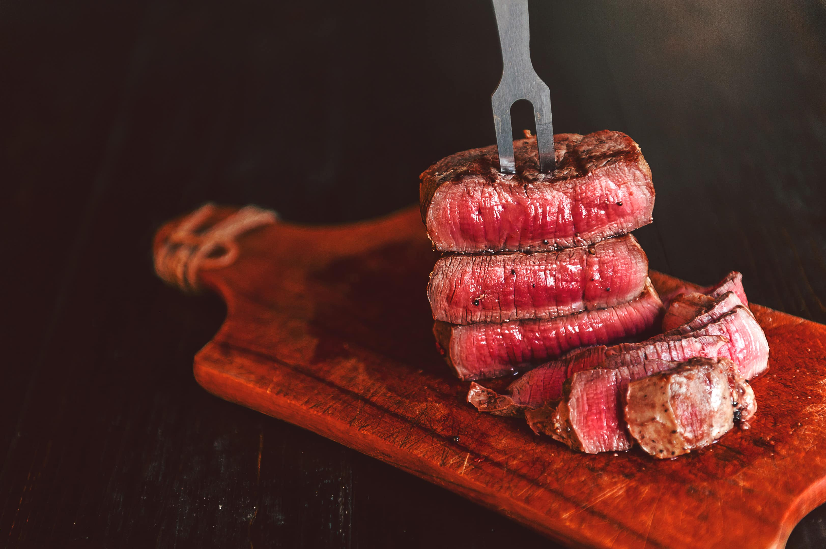 Beef steak with fork on wooden board