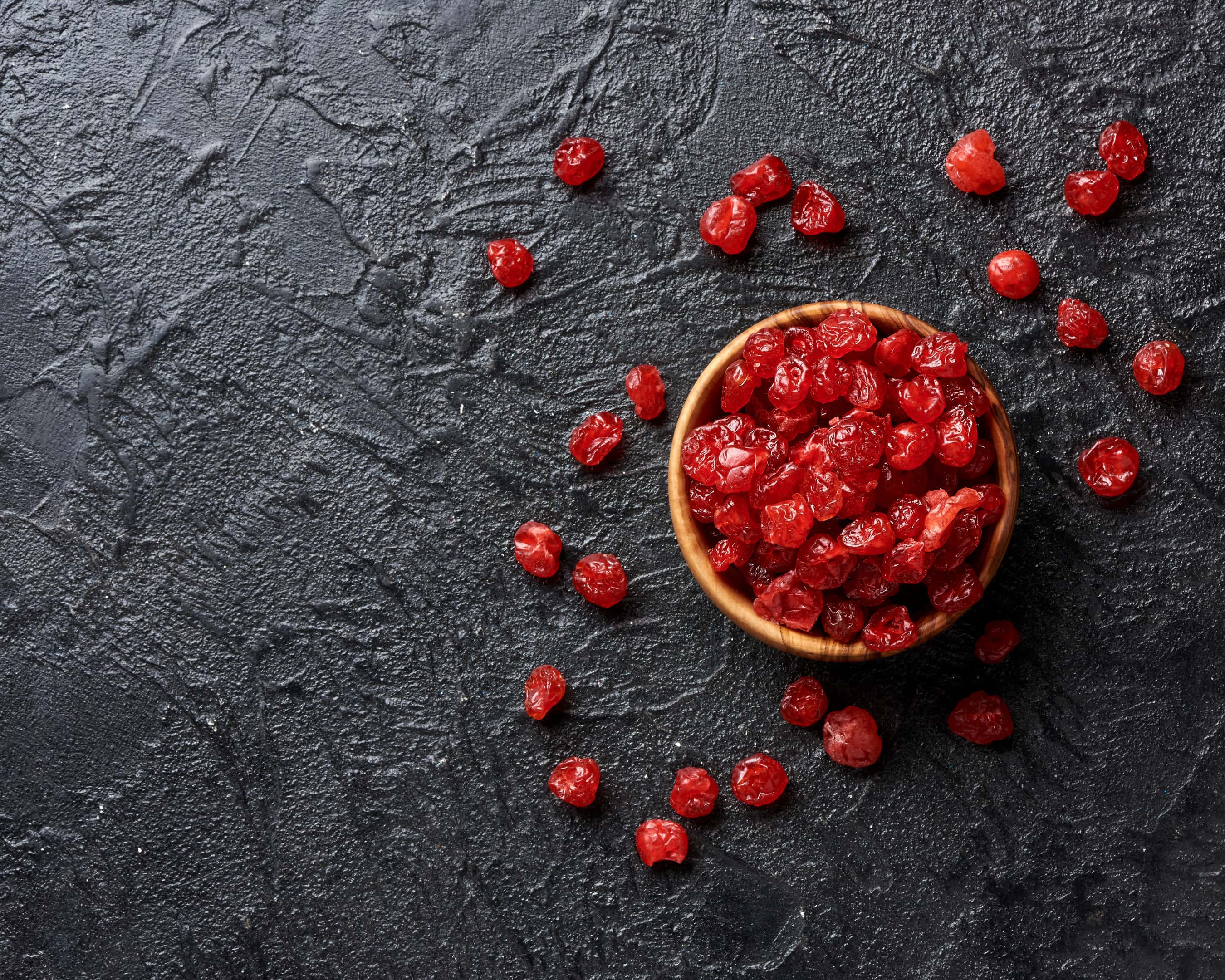 Dried red cherries on black surface