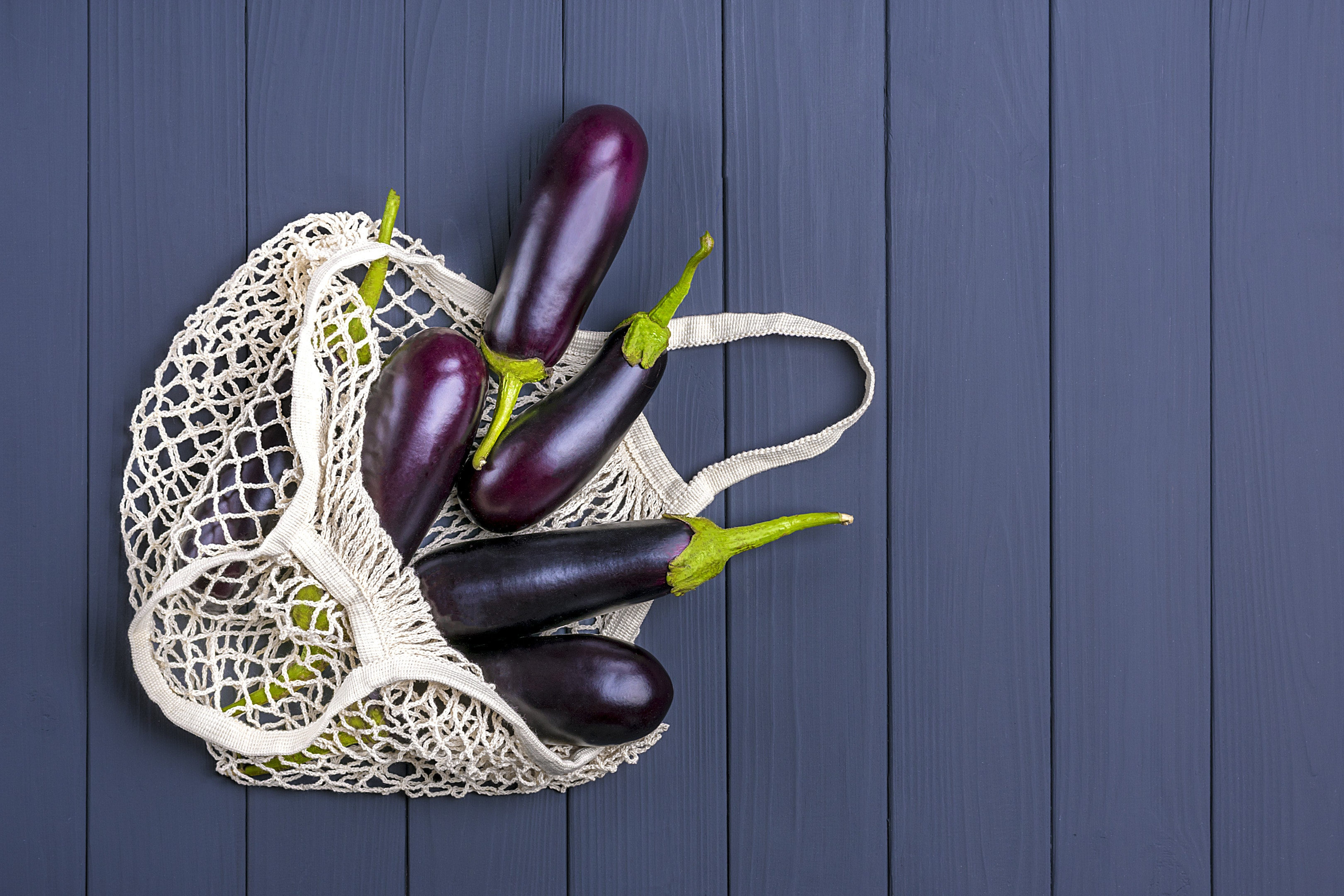 Eggplants in eco friendly mesh shopping bag on grey wooden table