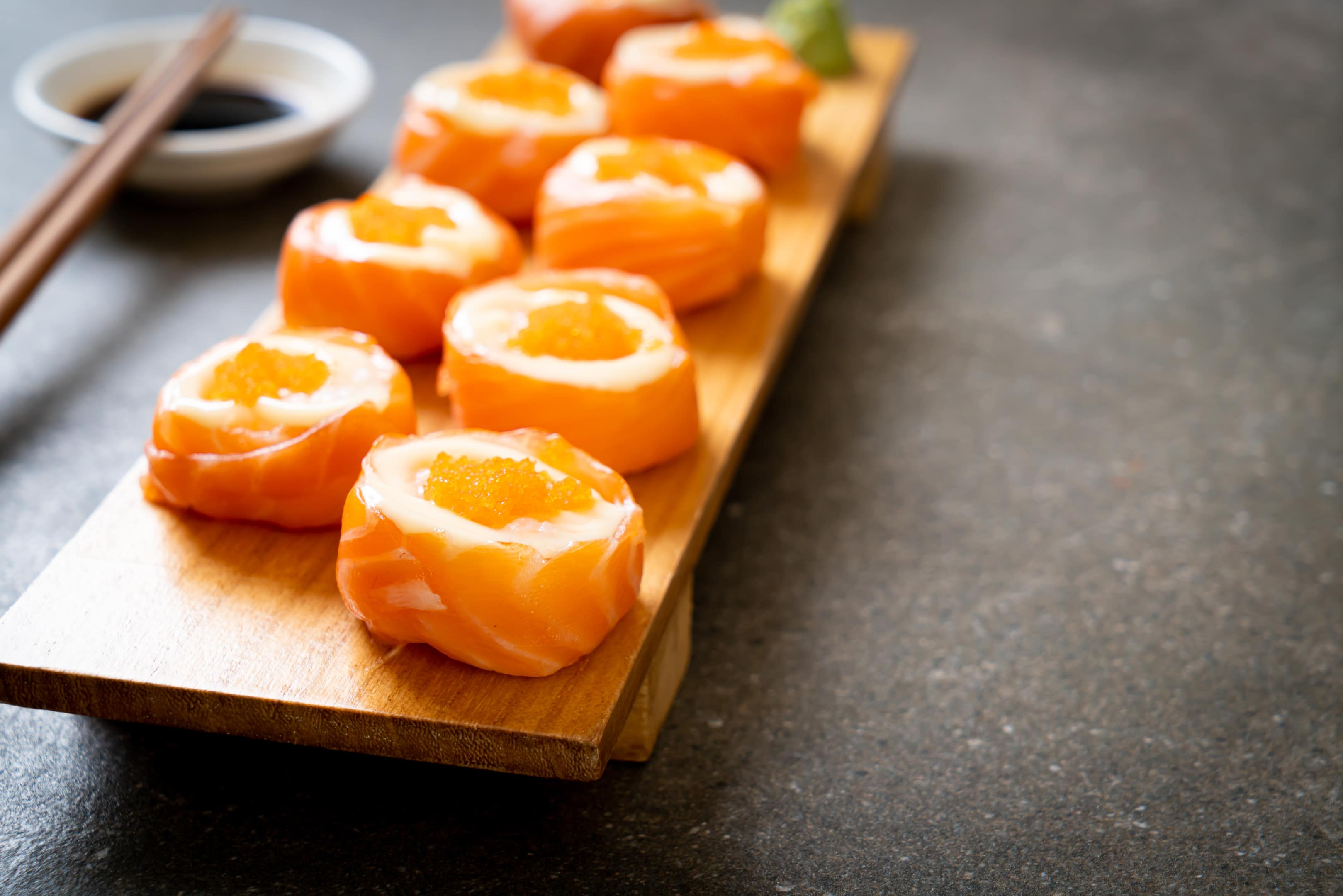 Fresh salmon sushi roll with shrimp egg on wooden board