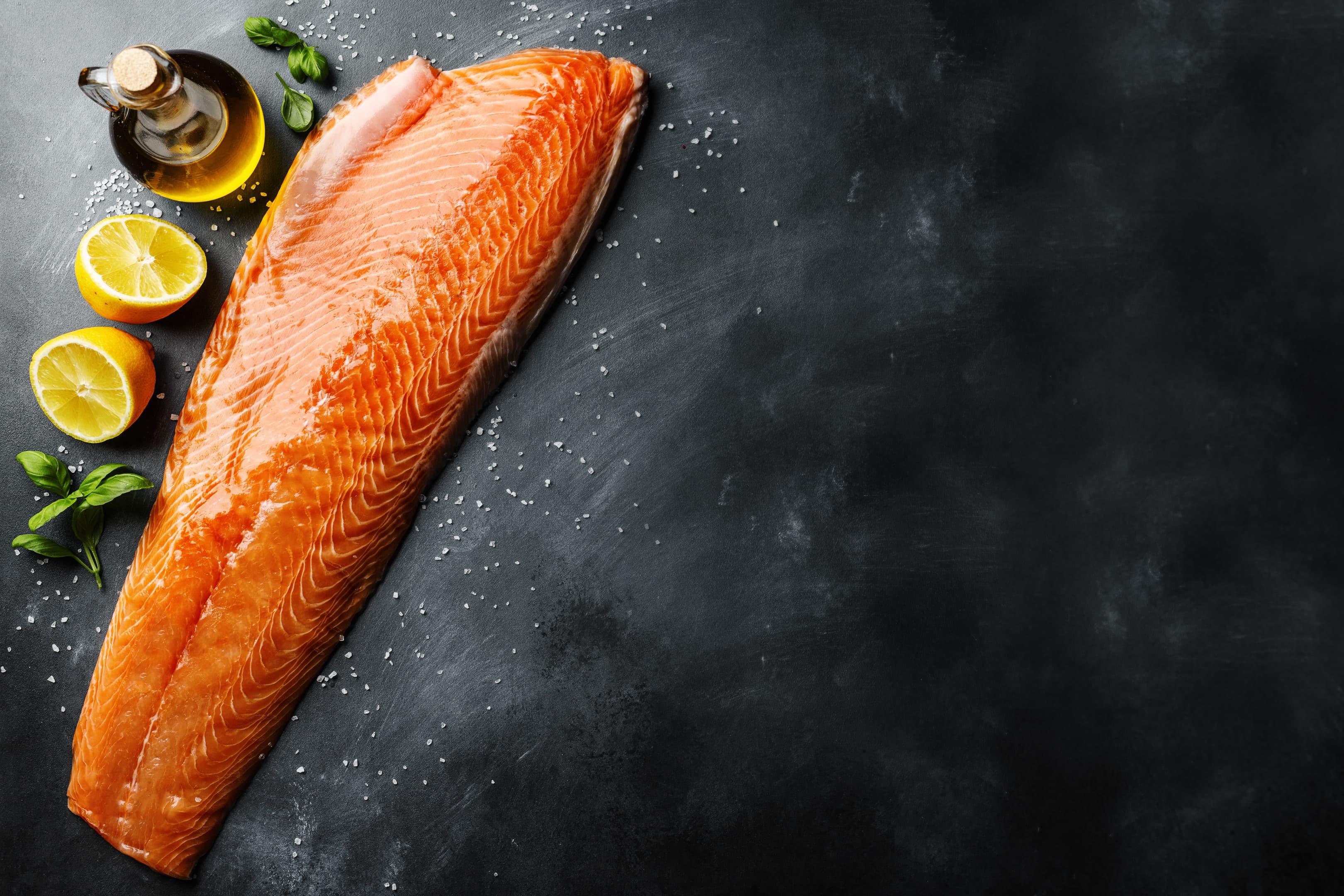 Fresh salmon with lemon on kitchen table