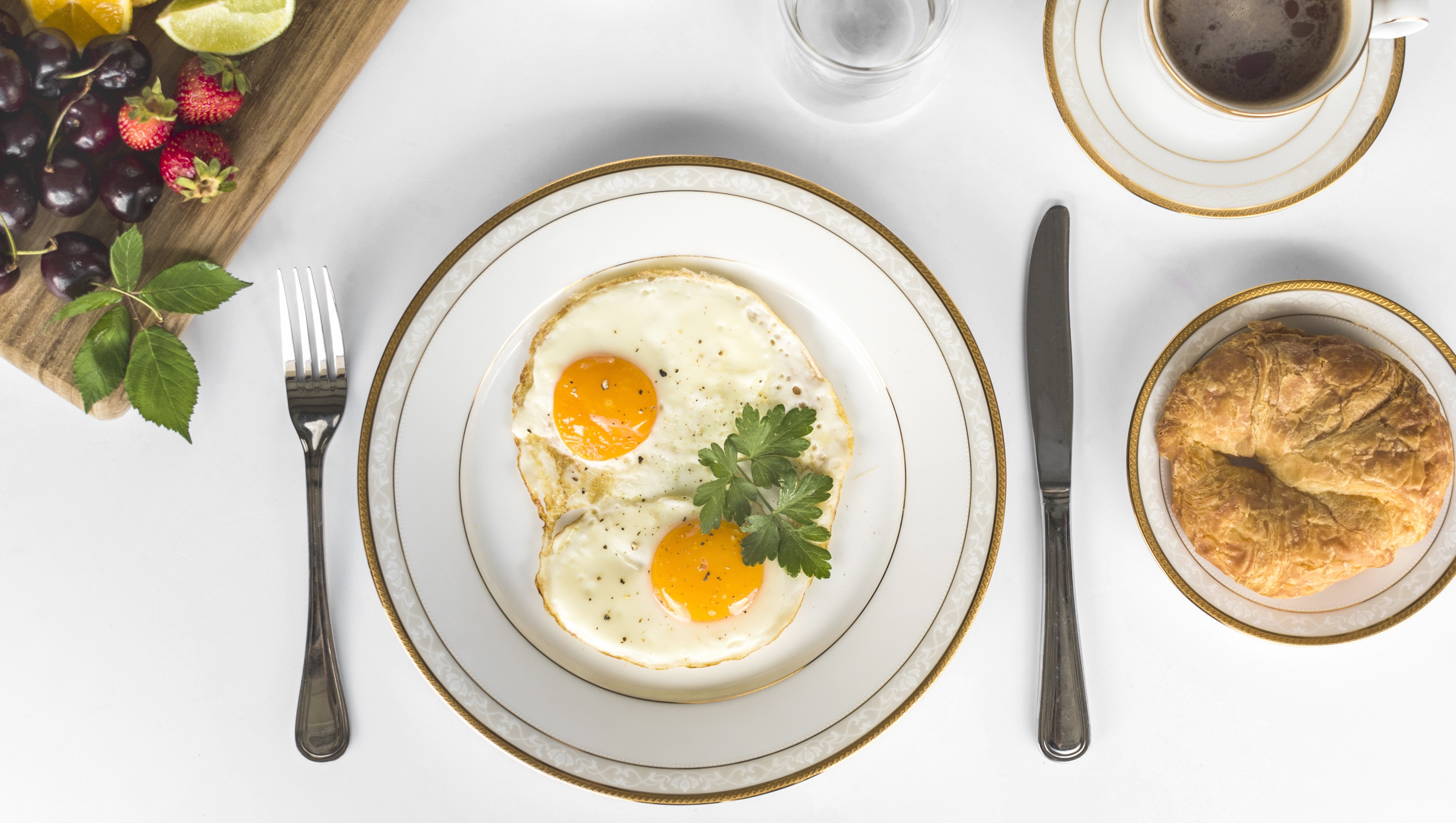 Fried eggs with bread and fruits breakfast on white background