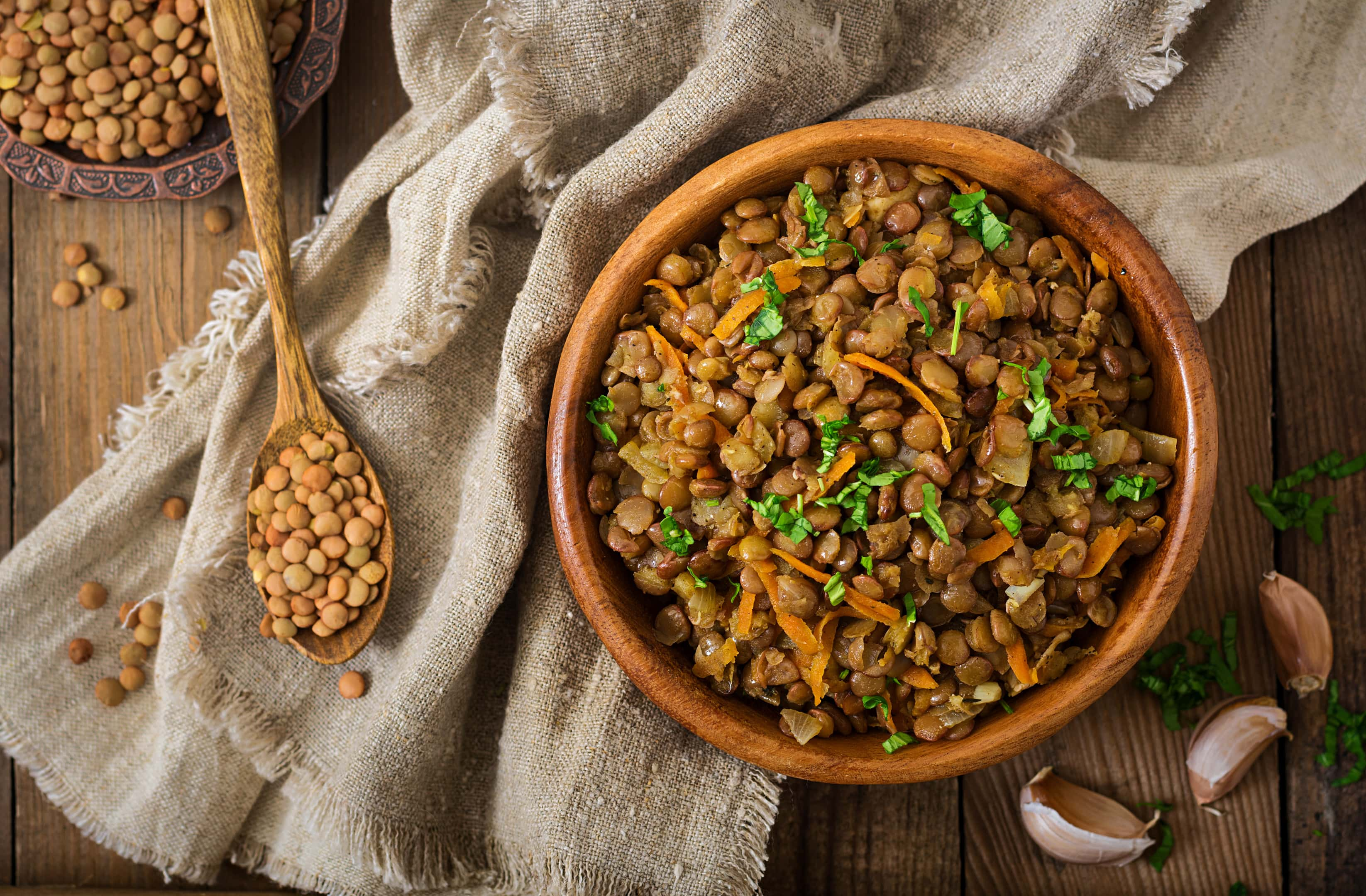 Lentil with carrot and onion in wooden bowl