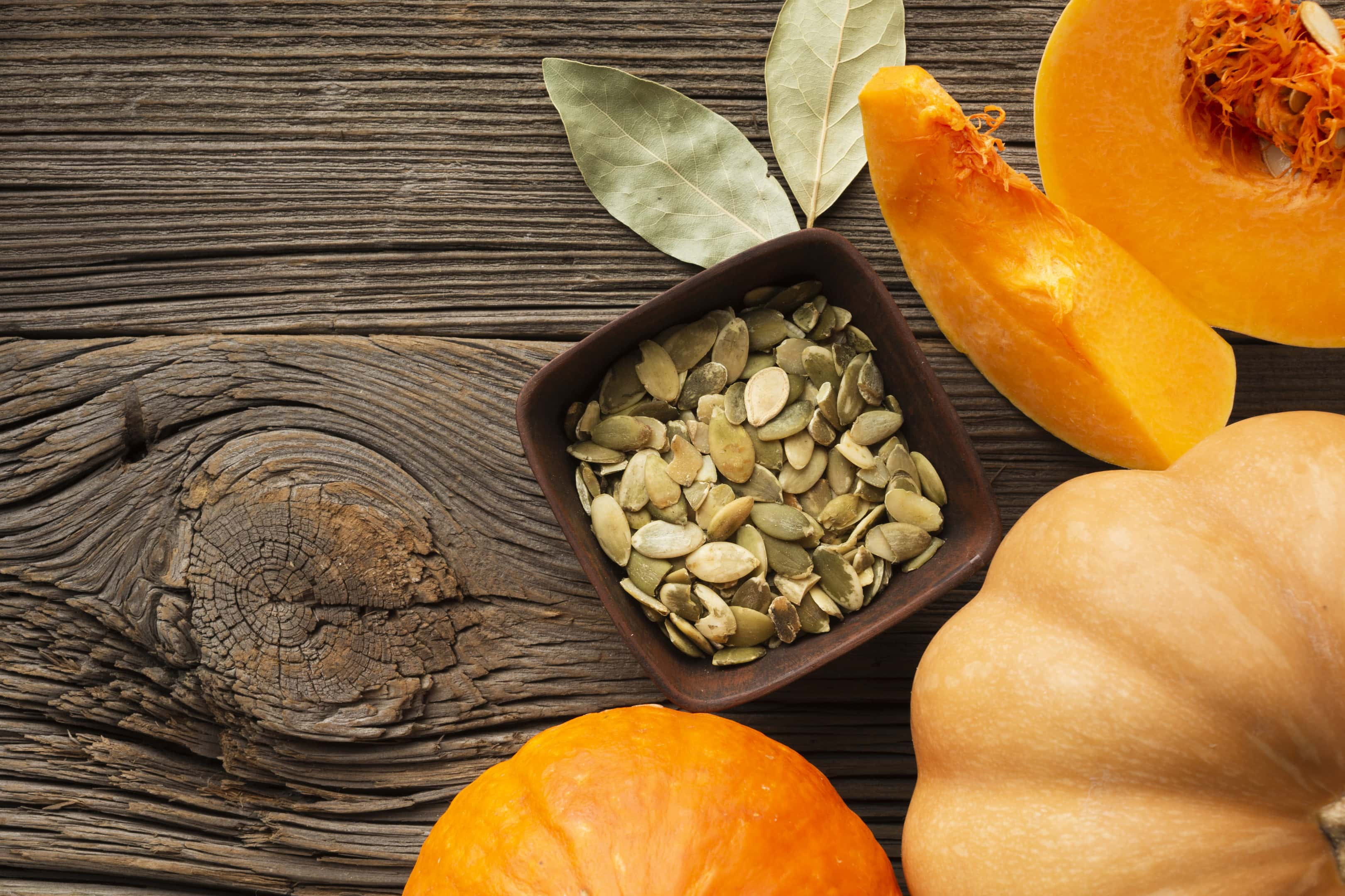 Pumpkin seeds with pumpkins on wooden table