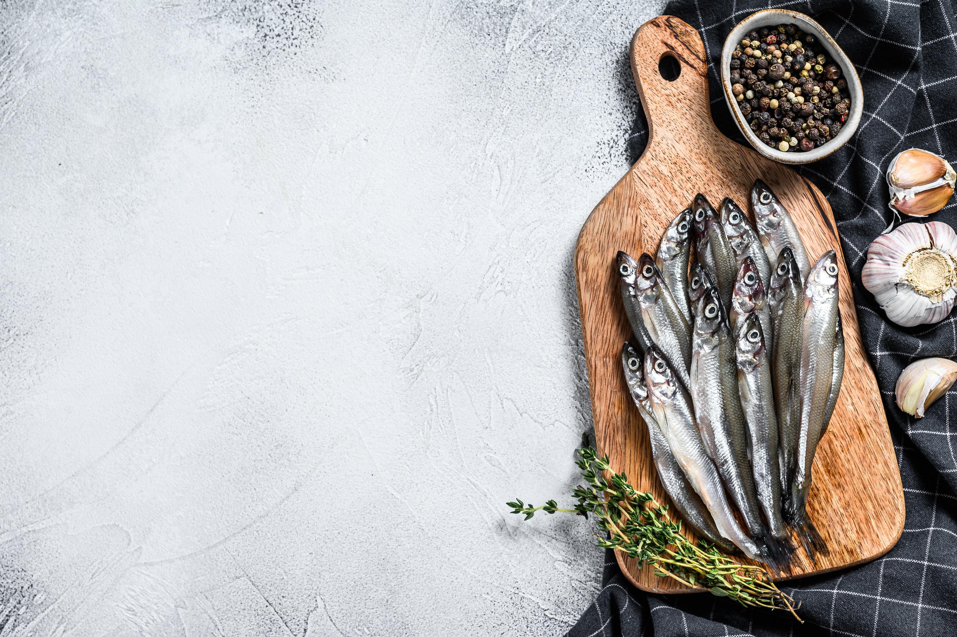 Raw fresh sardines on cutting board