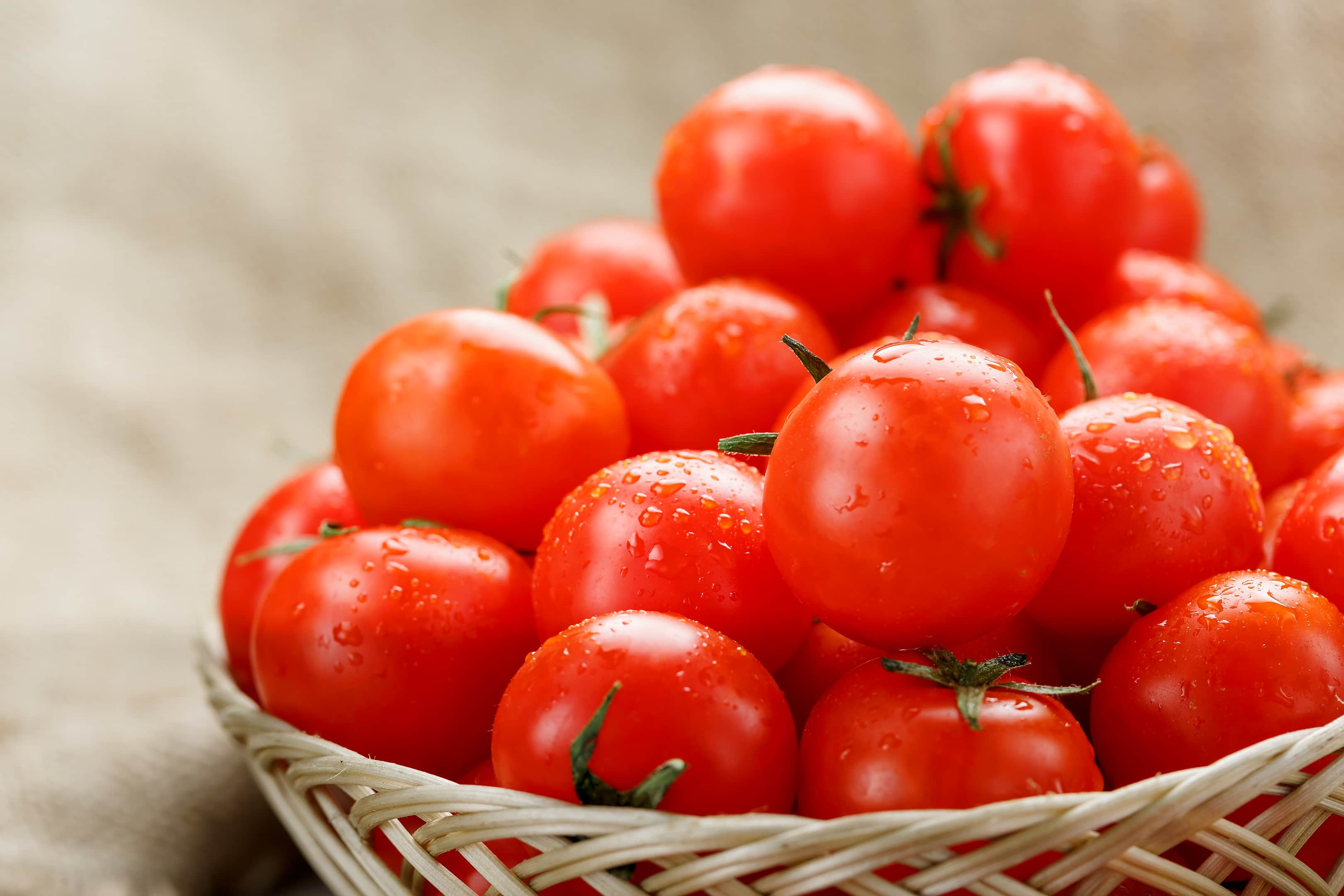 Ripe cherry tomatoes in basket on wooden table