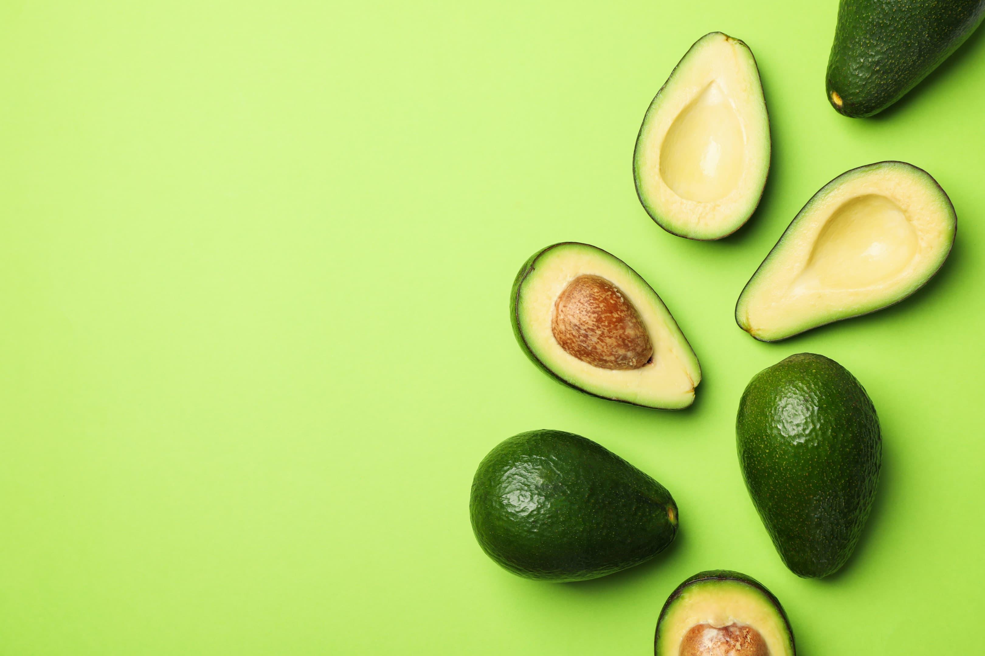 Ripe fresh avocado on green background