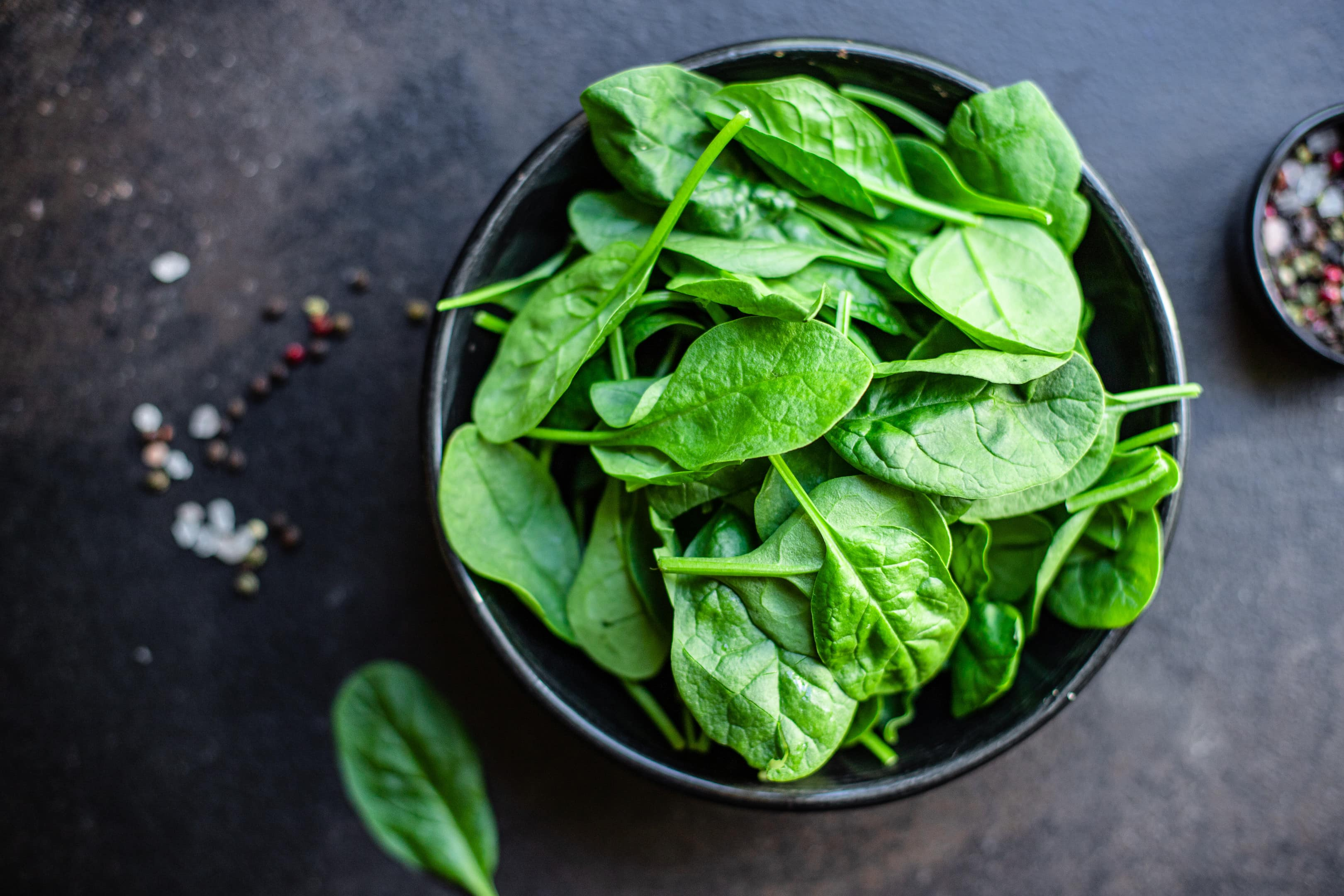 Spinach leaves in ceramic plate on kitchen table