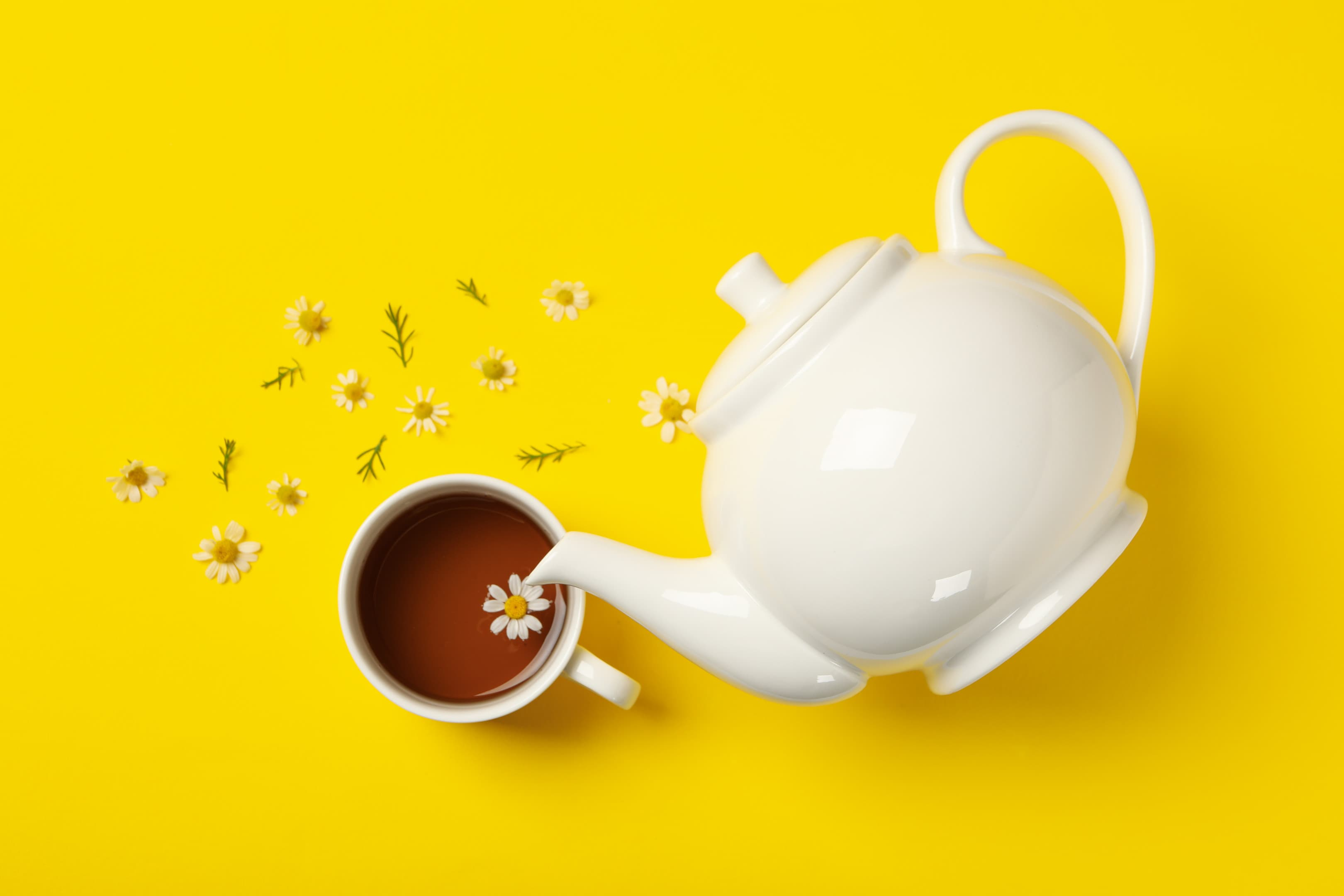 Teapot and cup of chamomile tea on yellow background