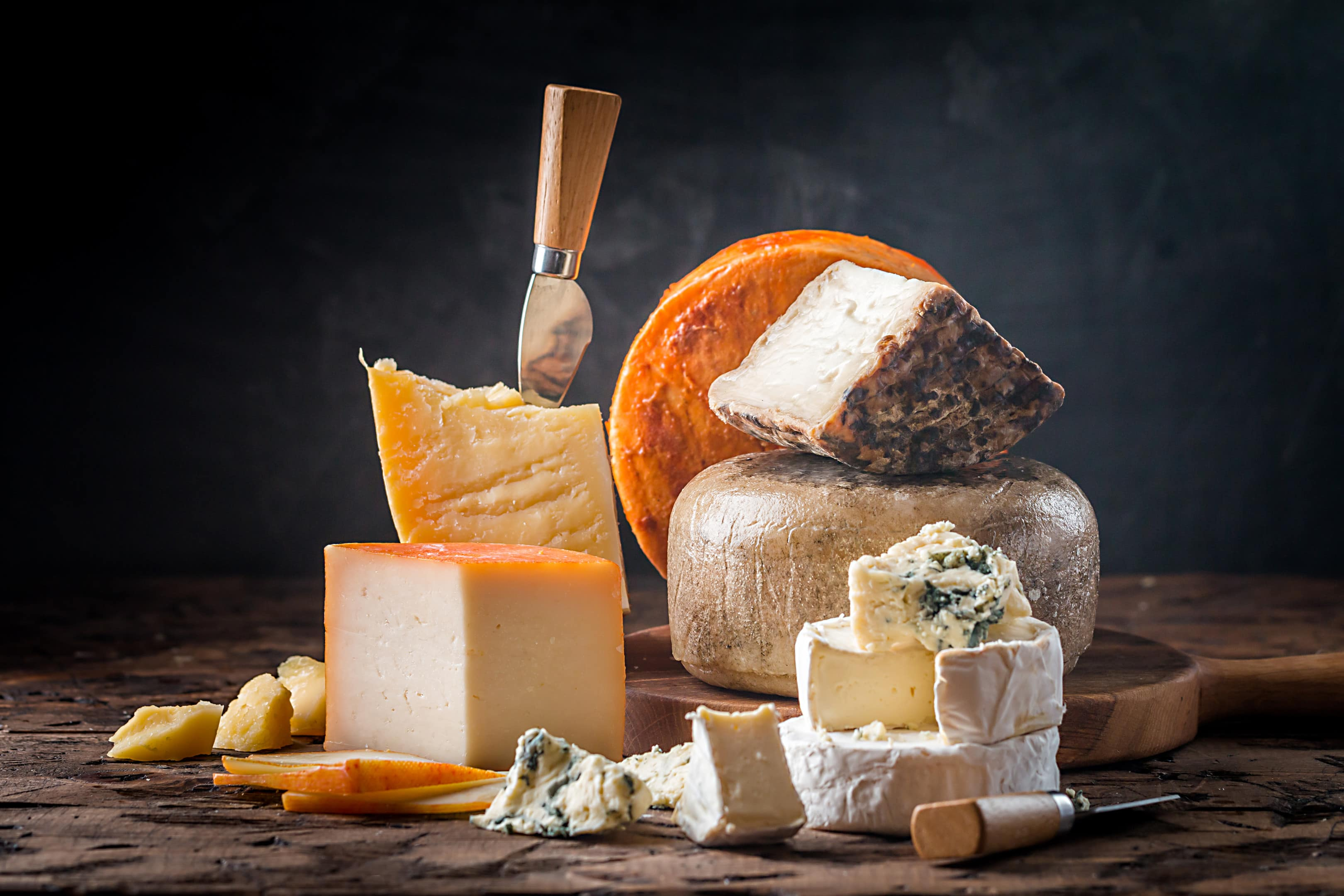 Various types of cheese on wooden table