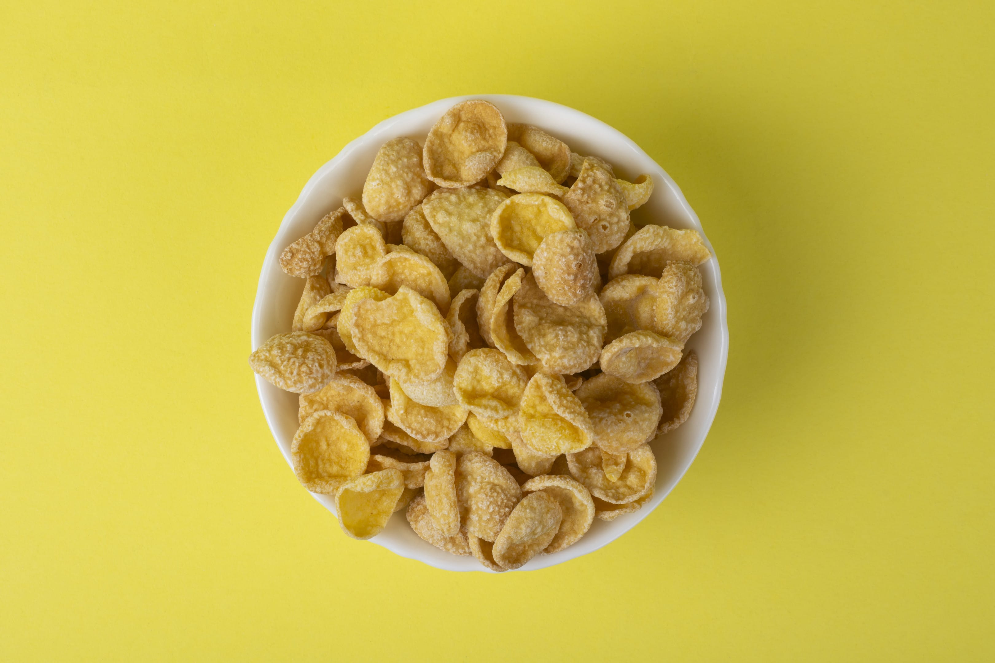 Bowl of Cornflakes on Yellow Table