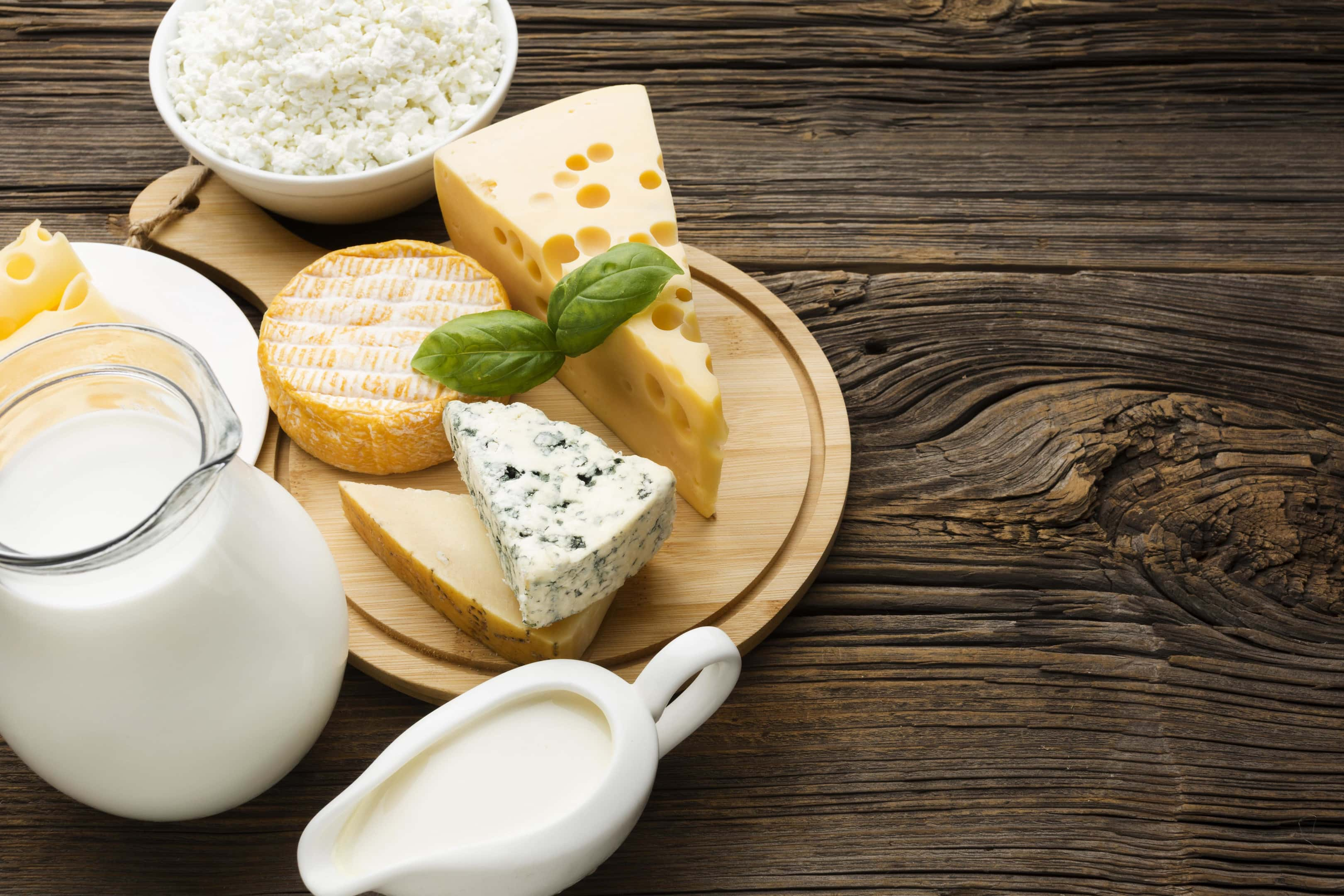Cheese With Milk on Wooden Table