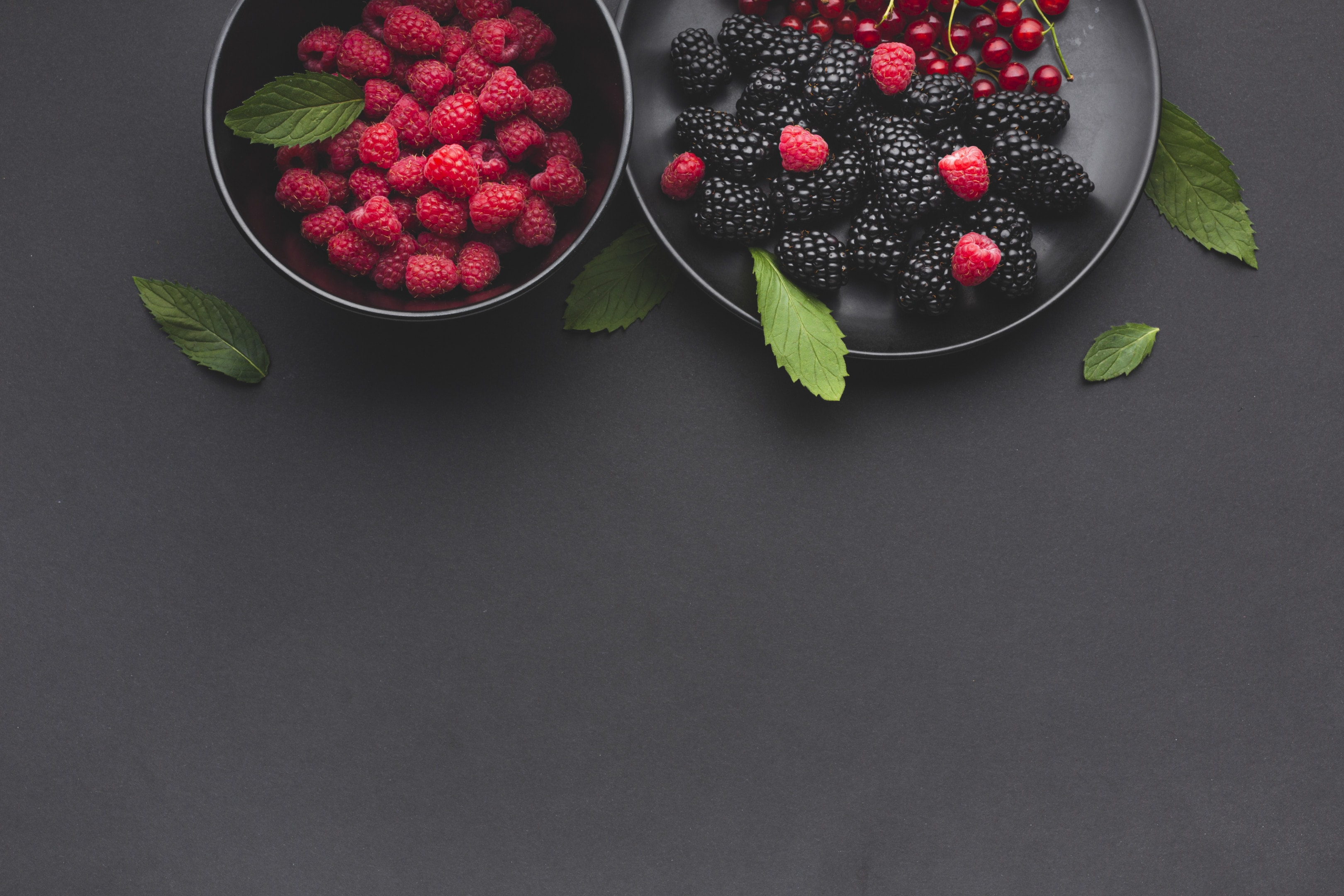 Plate and Bowl of Fresh Berries on Dark Table