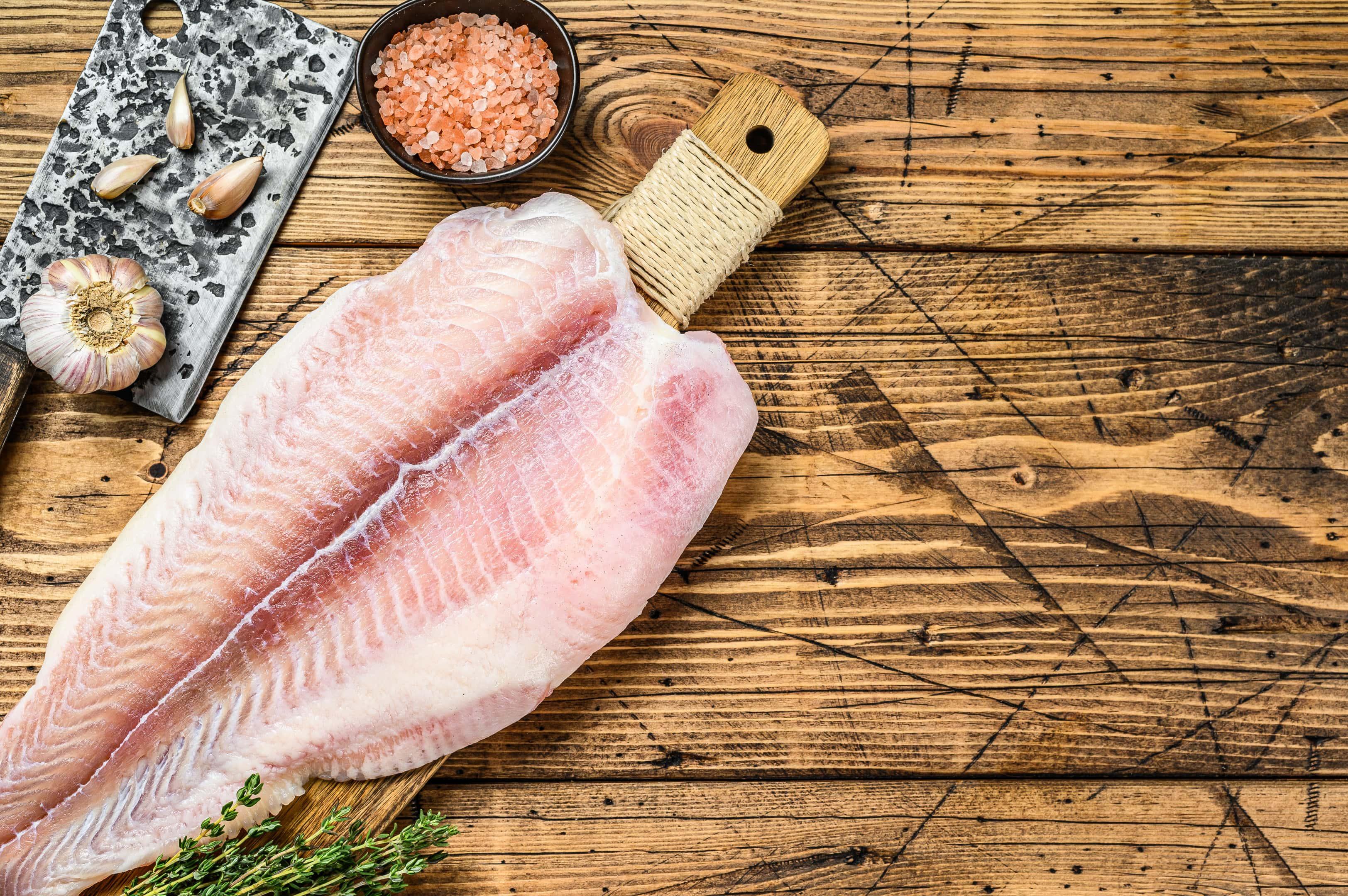 Raw Fillet of Cod Fish on Cutting Board