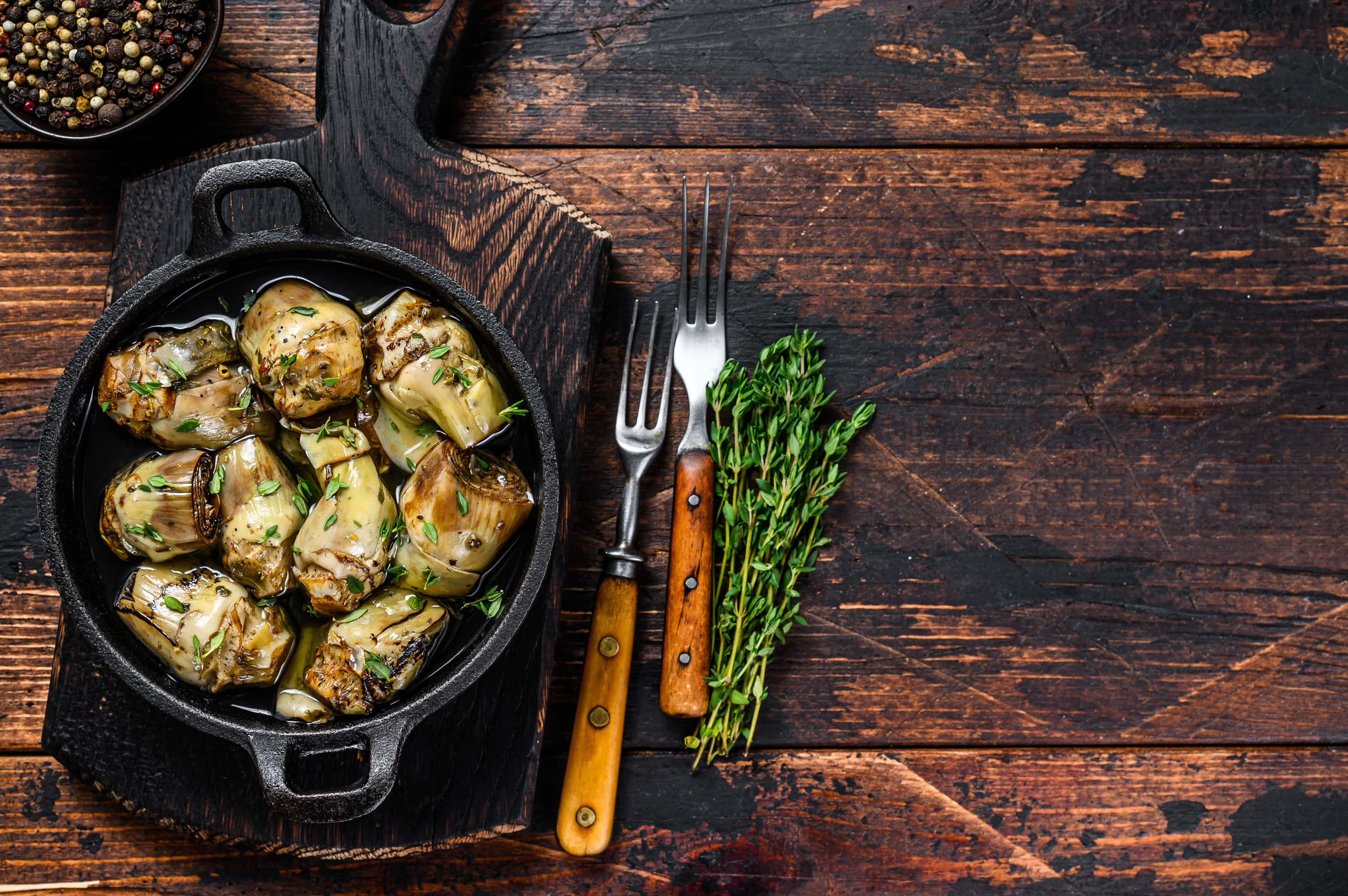Artichokes marinated with champagne vinegar in pan on wooden table