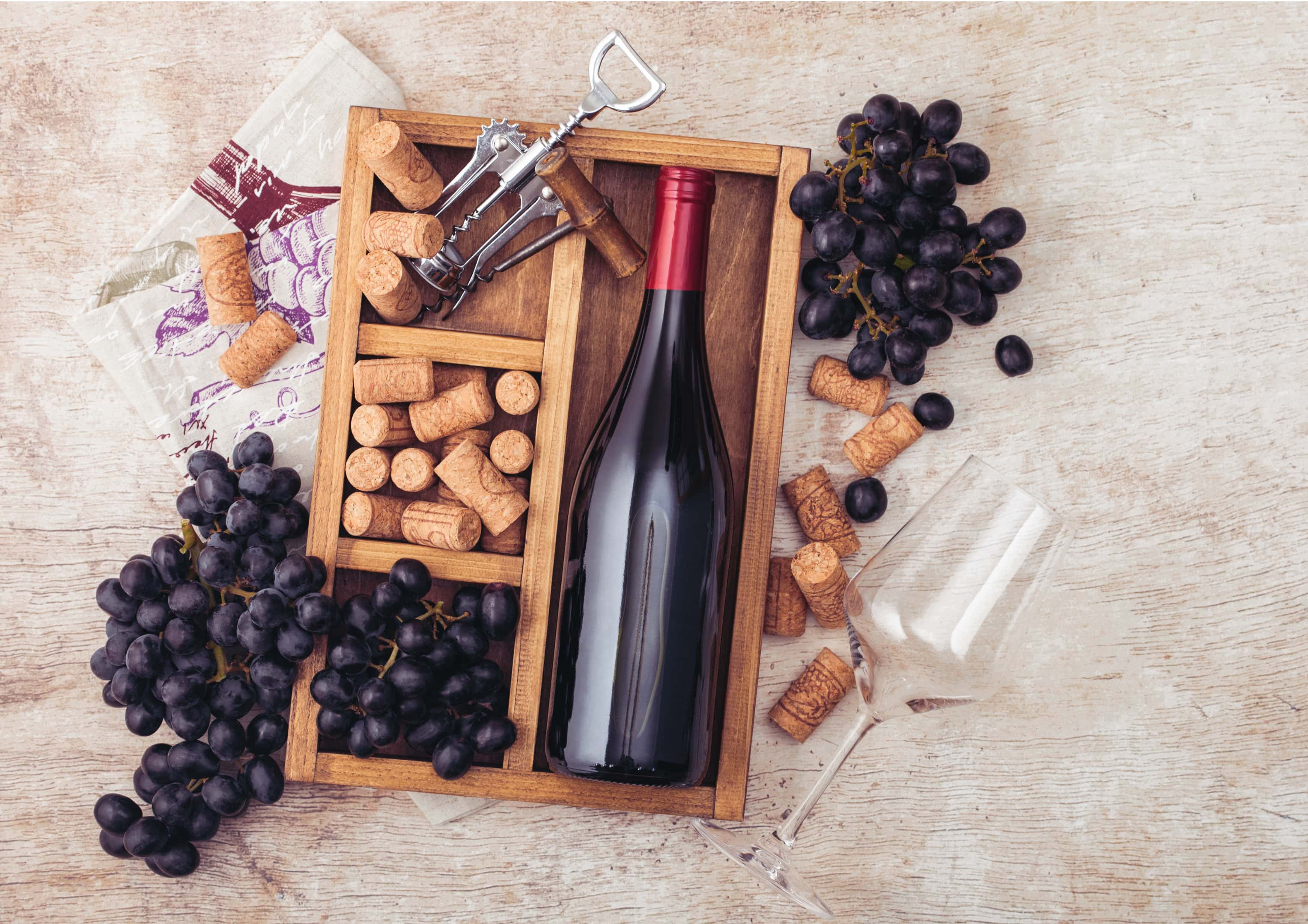 Bottle of red wine with corks and grapes in wooden box
