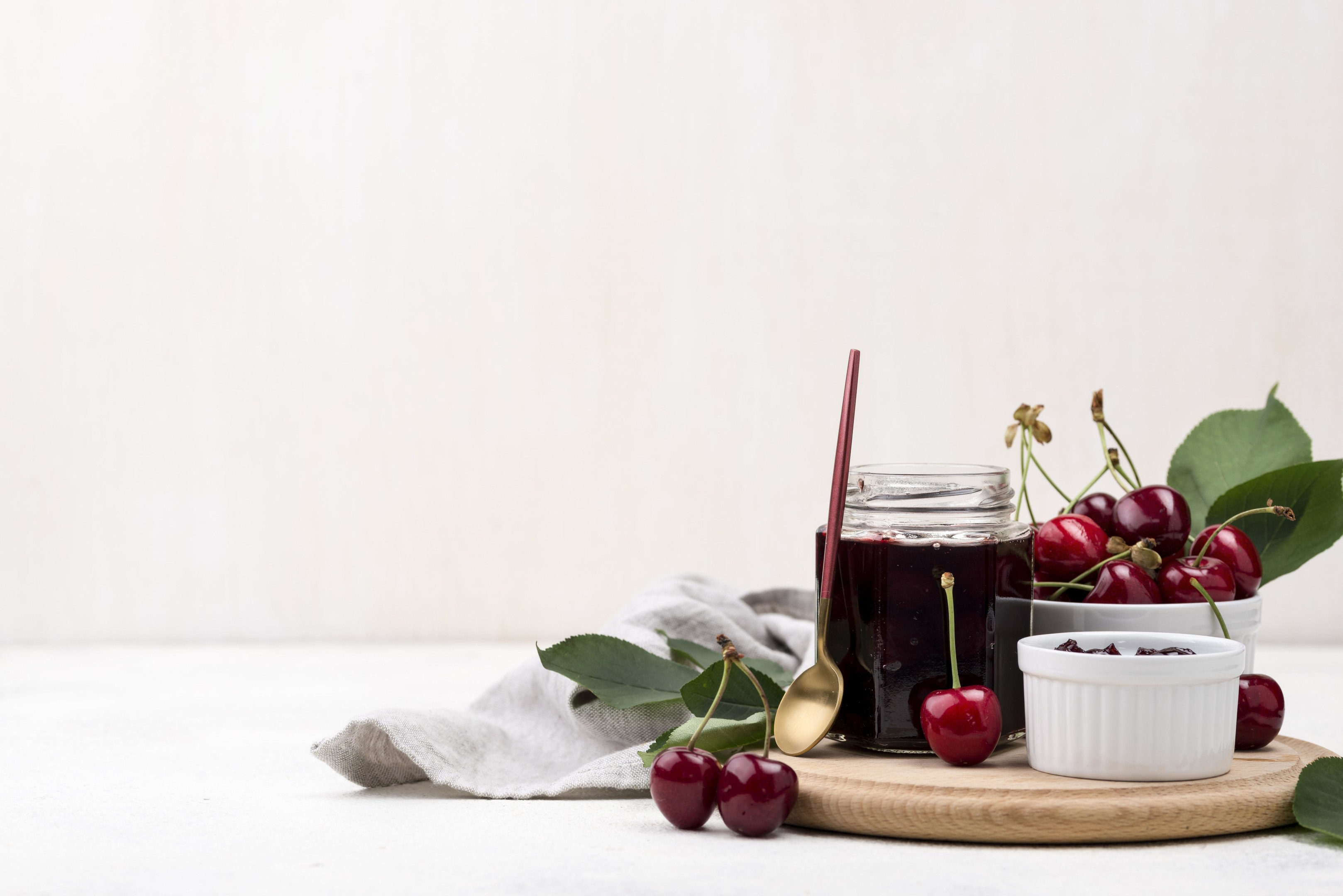Cherries and cherry jam on wooden board