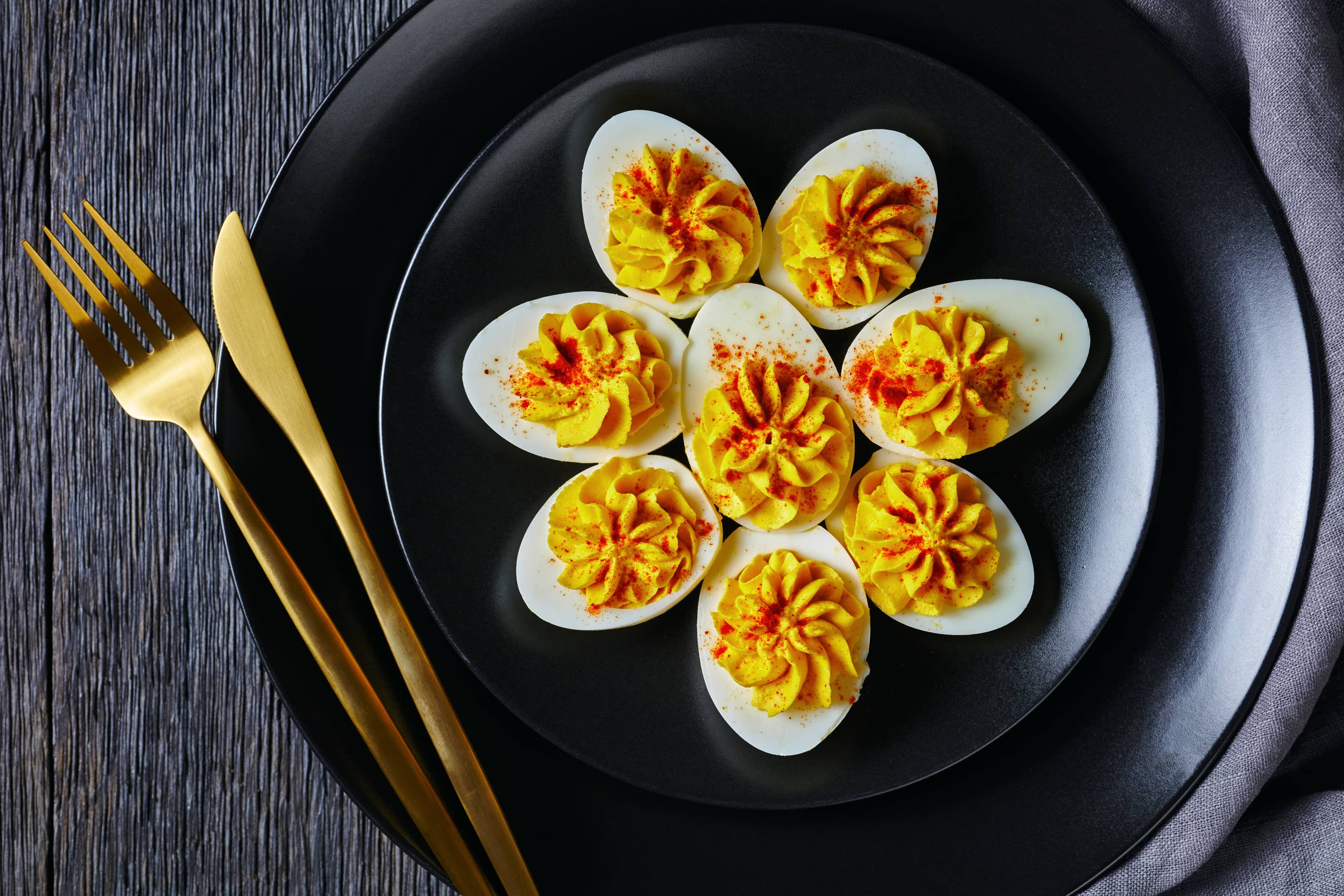 Classic deviled eggs filled with mustard mayonnaise white vinegar sprinkled with smoked paprika on black plate