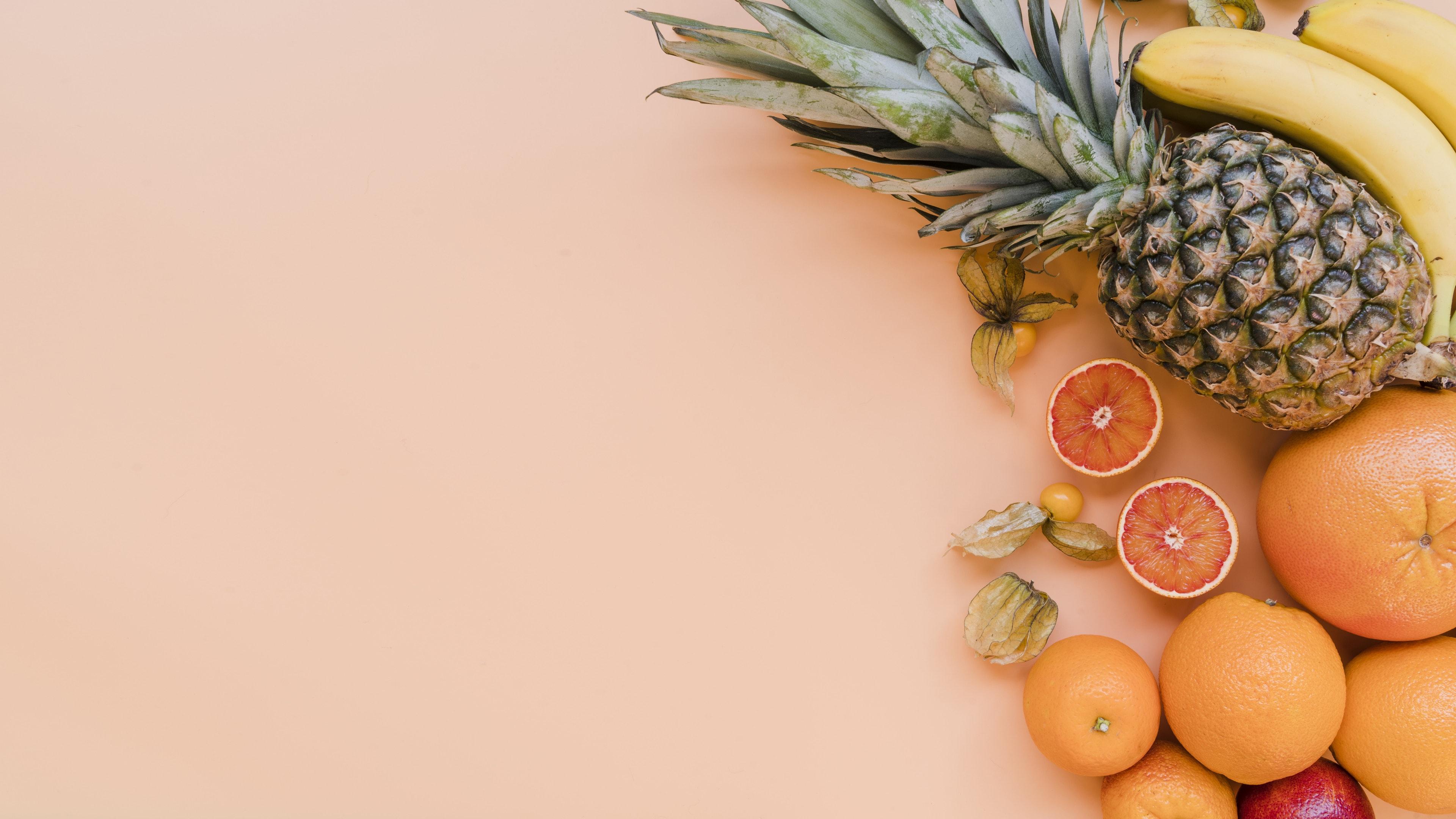 Delicious fresh fruits on orange background