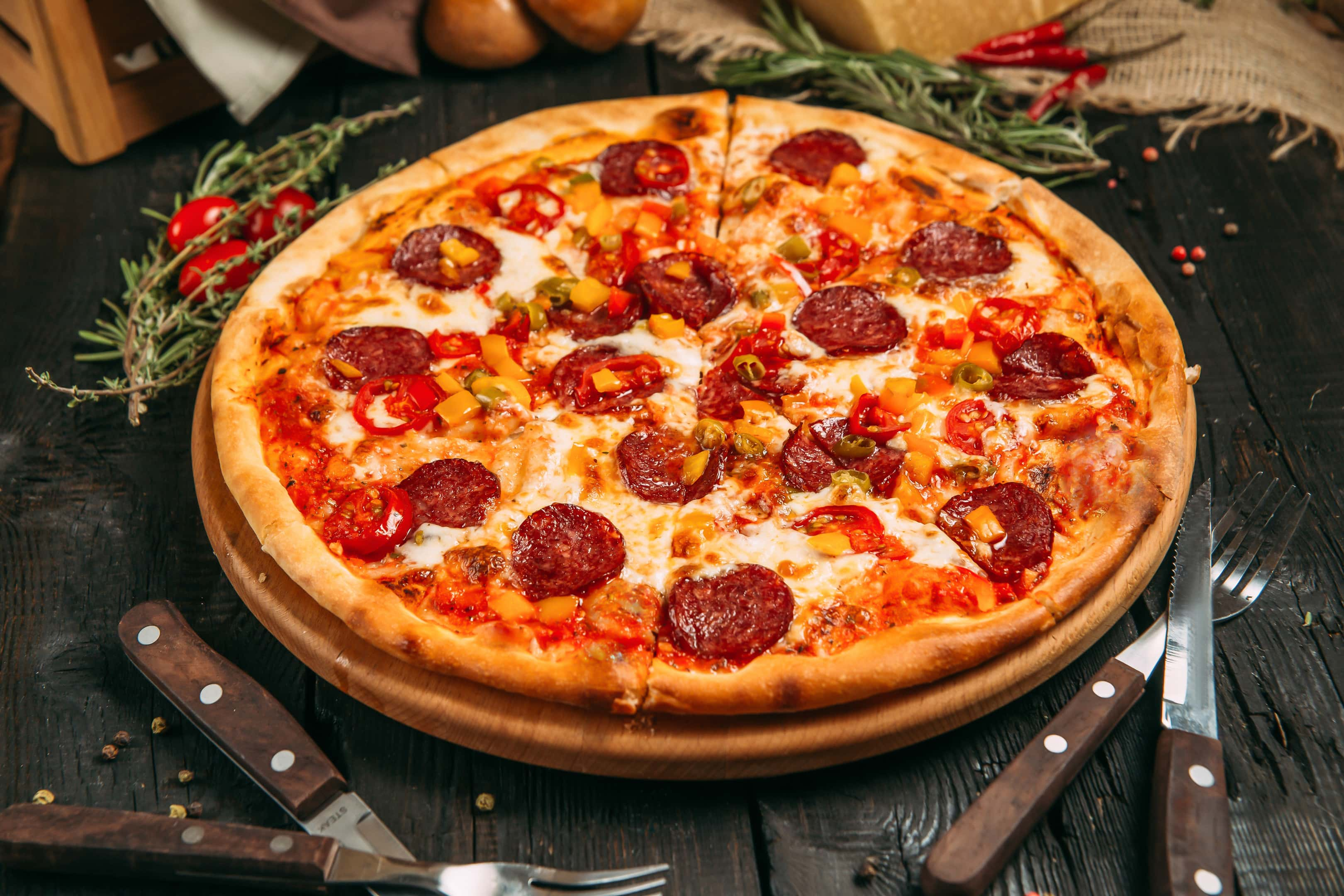 Delicious savory pizza with pepperoni and pepper on dark wooden table