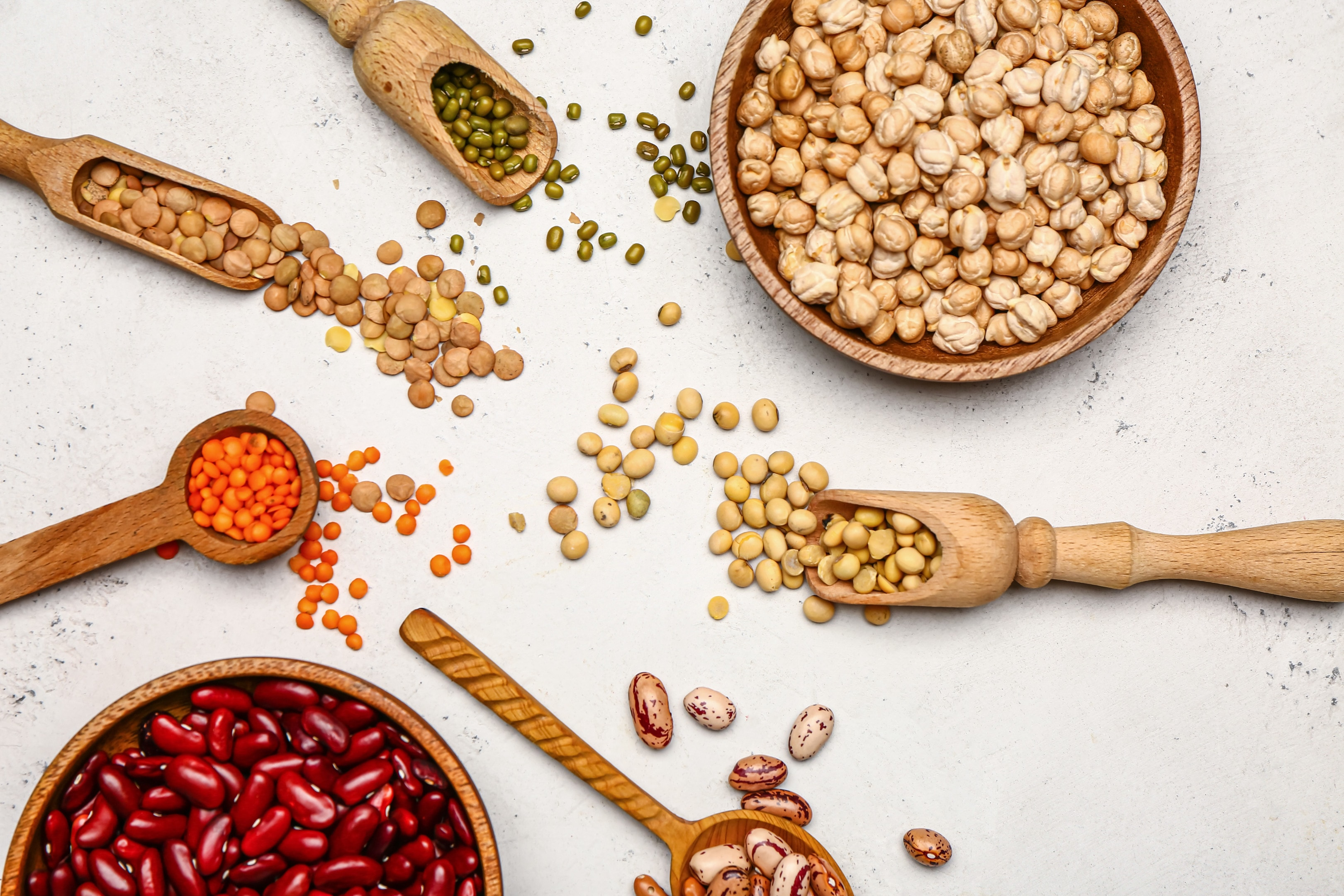 Different raw legumes on white table