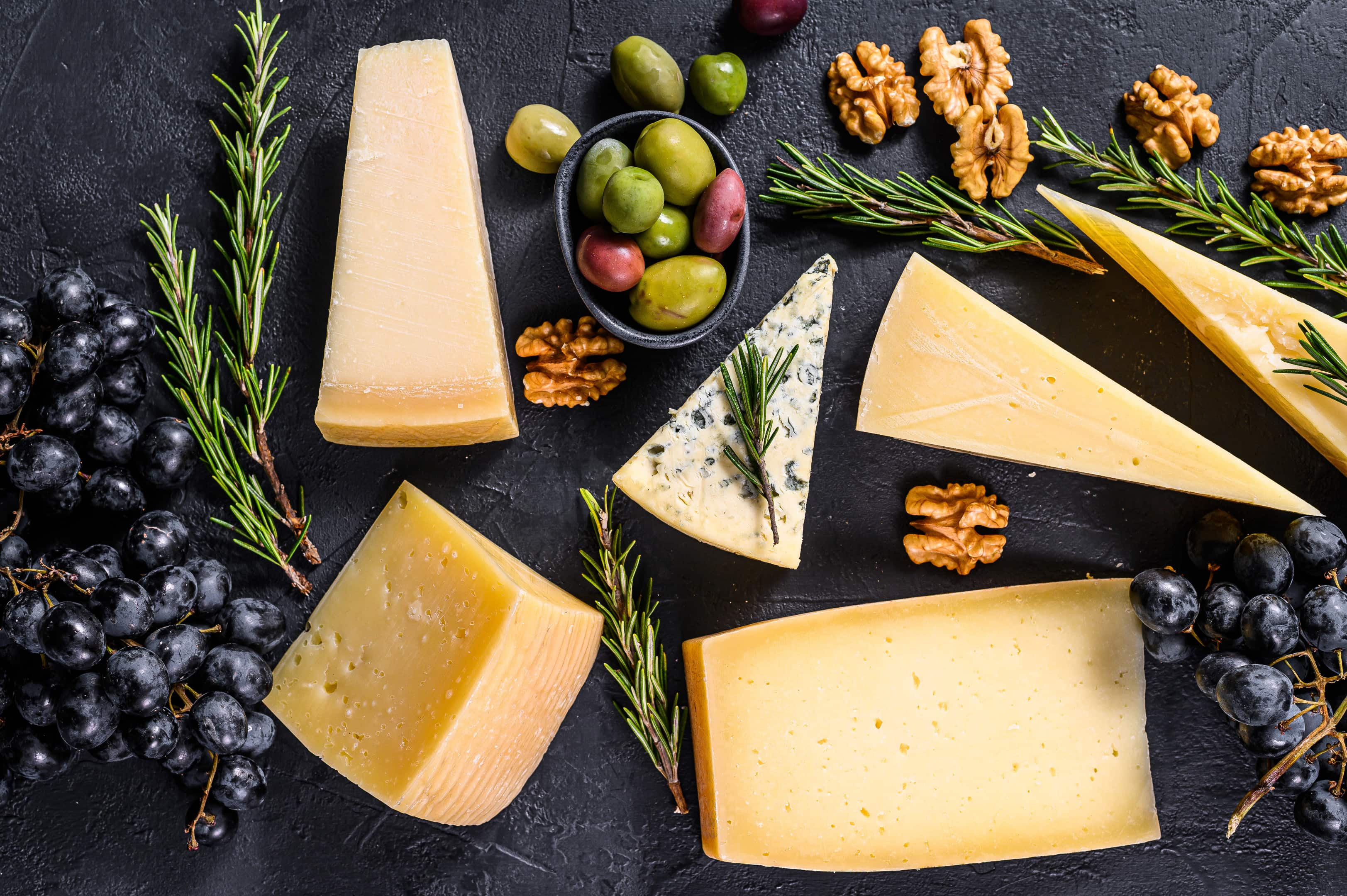 Different types delicious cheese with walnuts and grapes