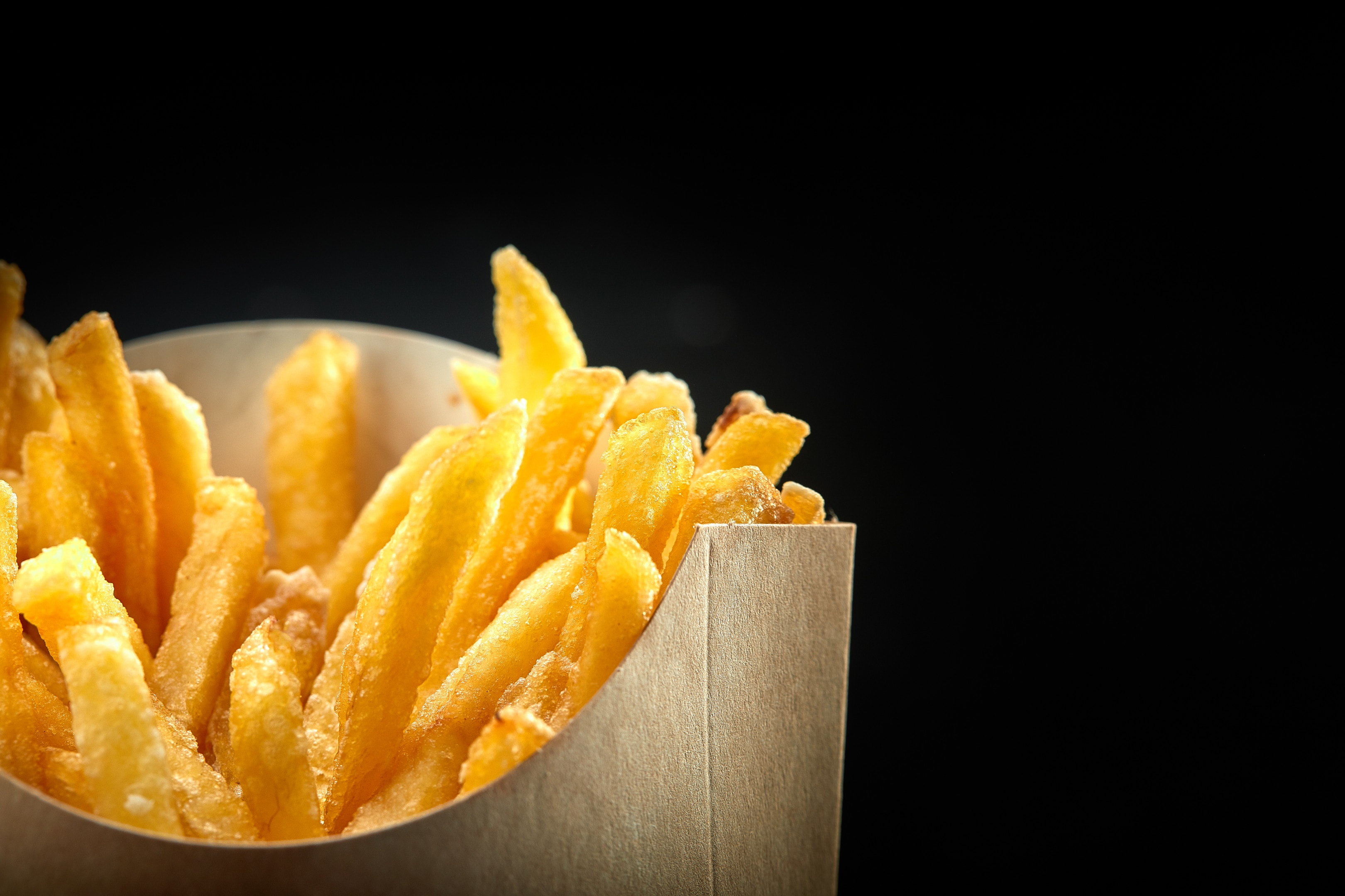 French fries in paper bag on black background