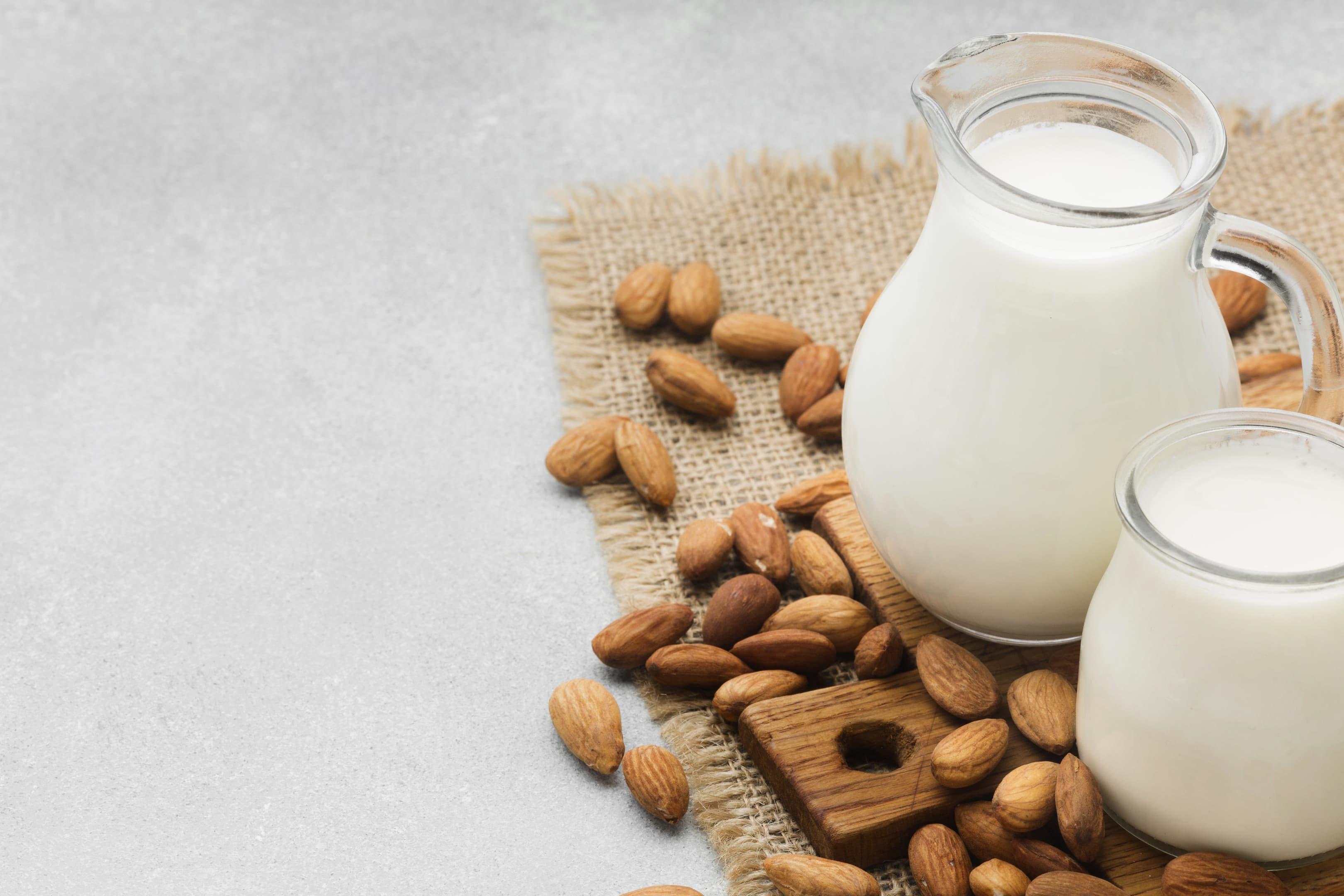 Fresh almond milk with almonds on white table