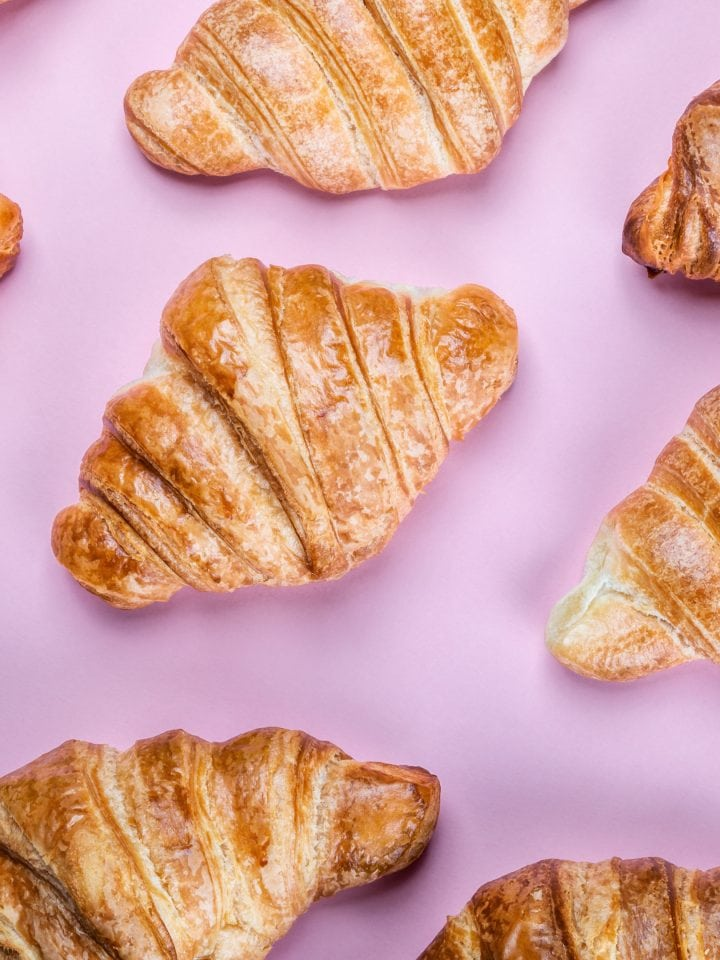 Freshly baked croissants on pink background