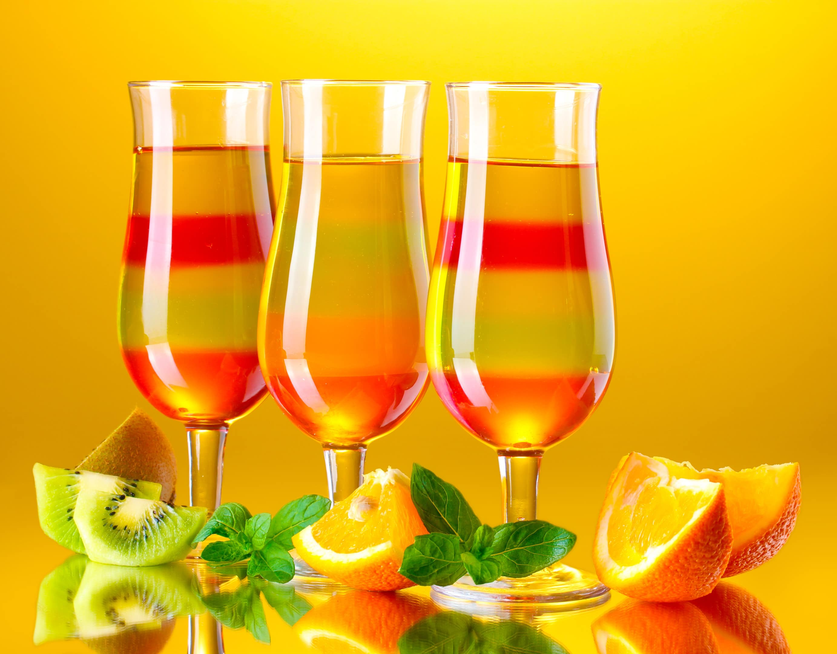Fruit jelly gelatin in tall glasses with fresh fruits on yellow background