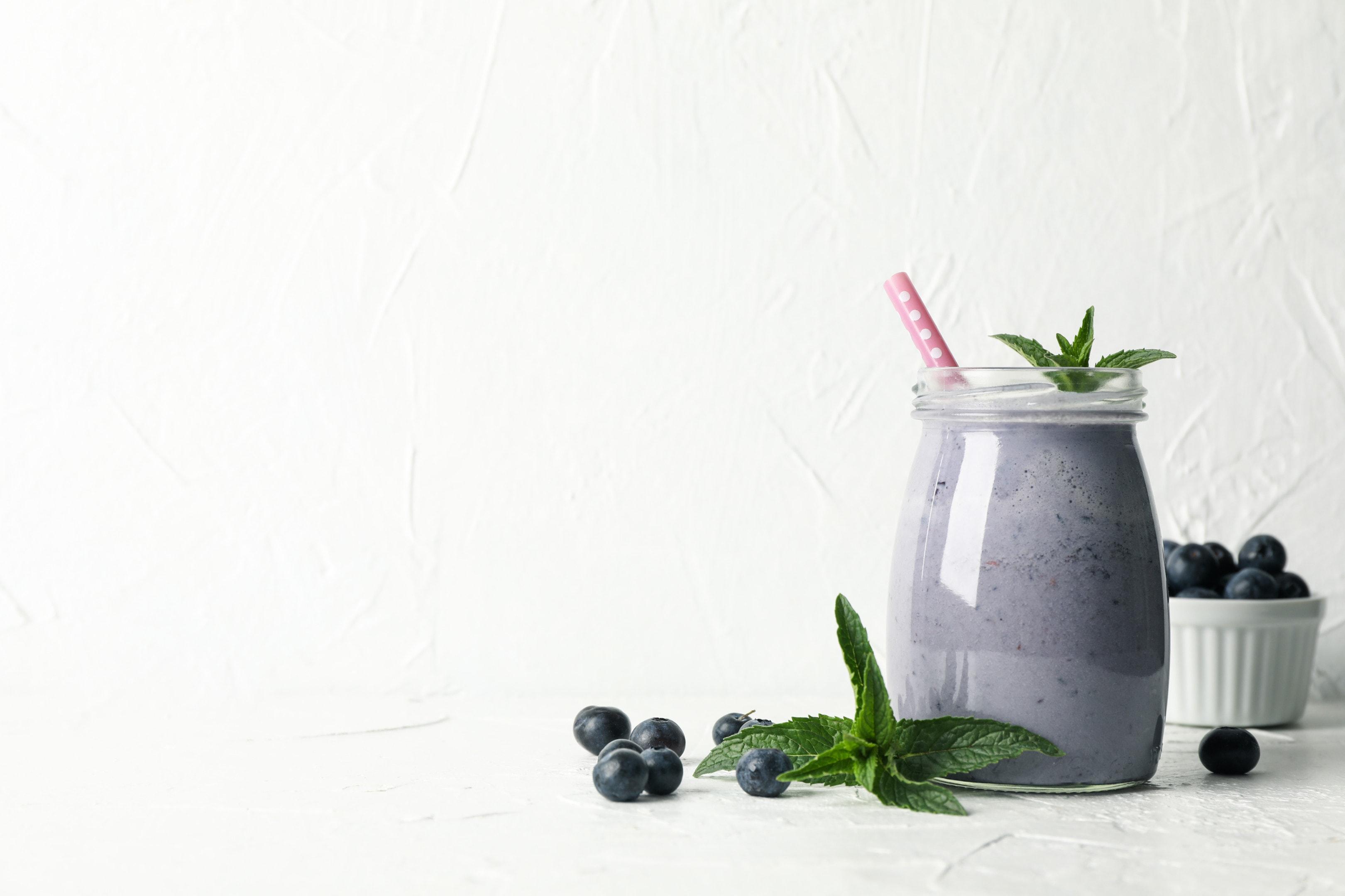 Glass of berry milkshake on white table