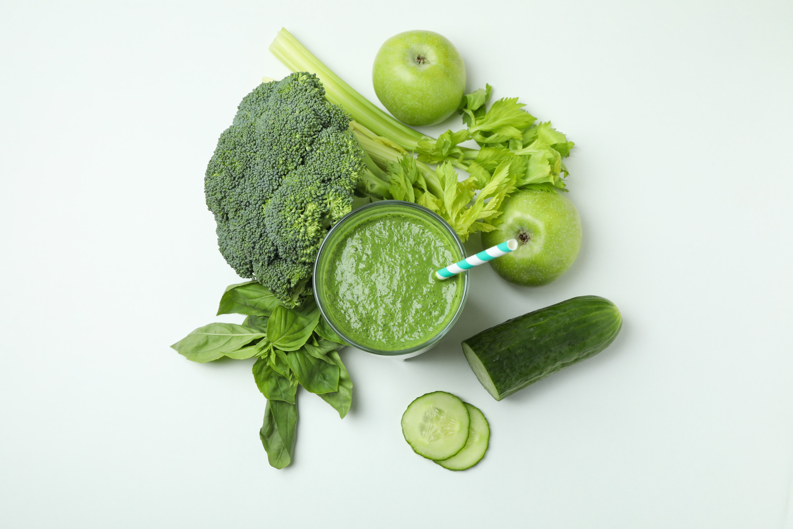 Glass of green smoothie and green leafy vegetable on white background