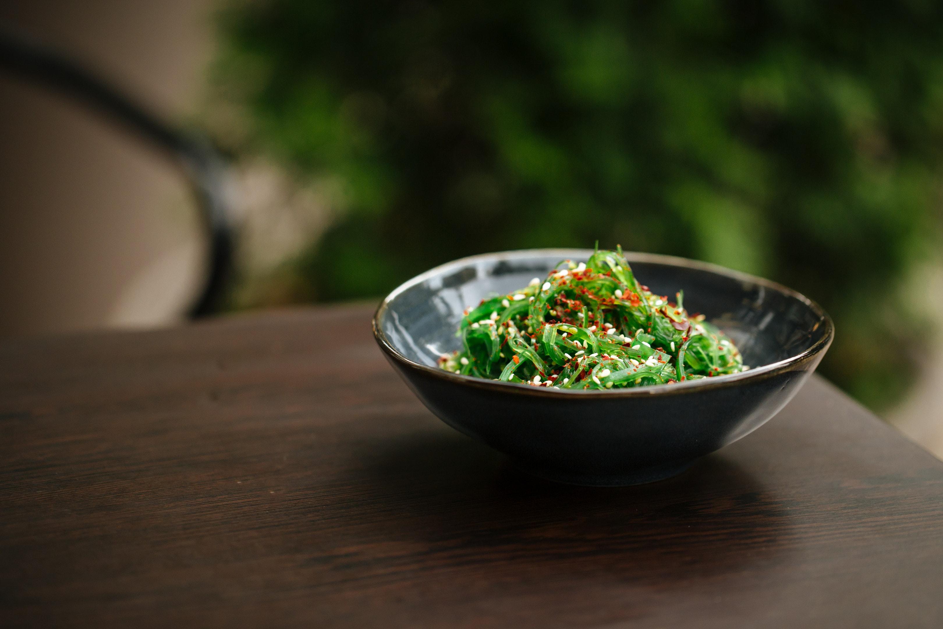 Green chuka seaweed salad in black bowl