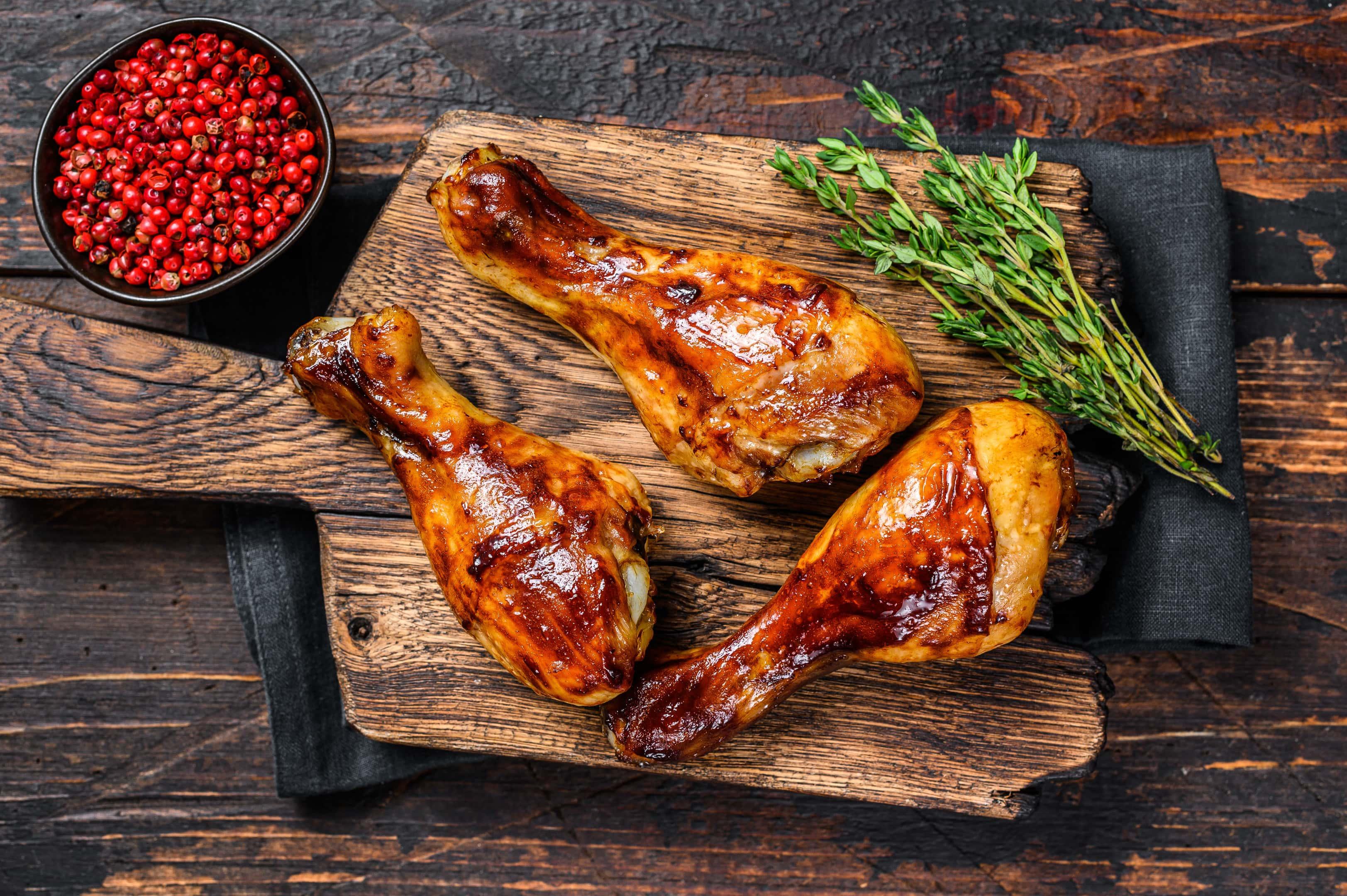 Grilled chicken drumsticks glazed with malt vinegar on wooden cutting board