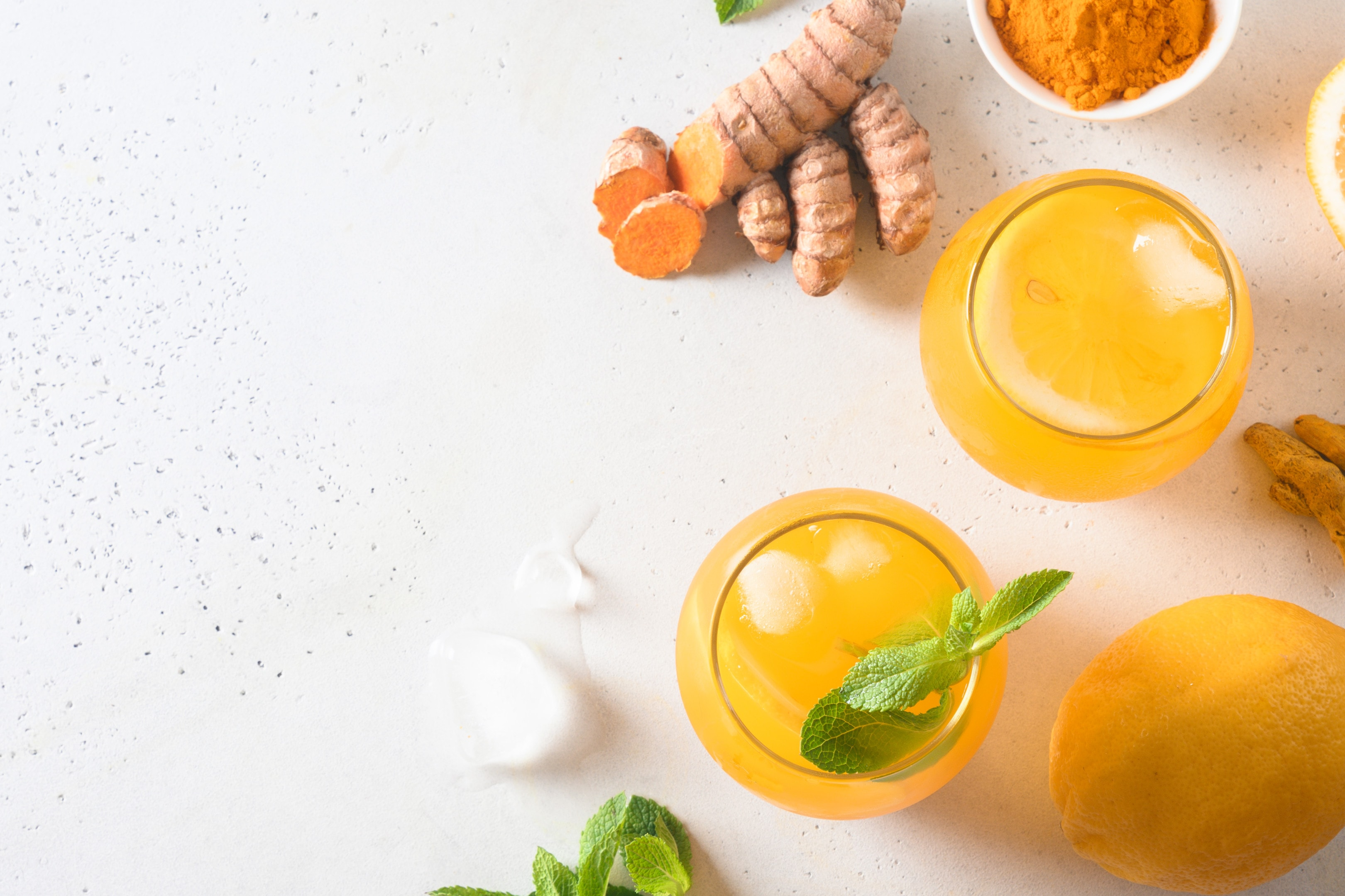 Jamu indonesian herbal beverage with natural ingredients turmeric and ginger on white table